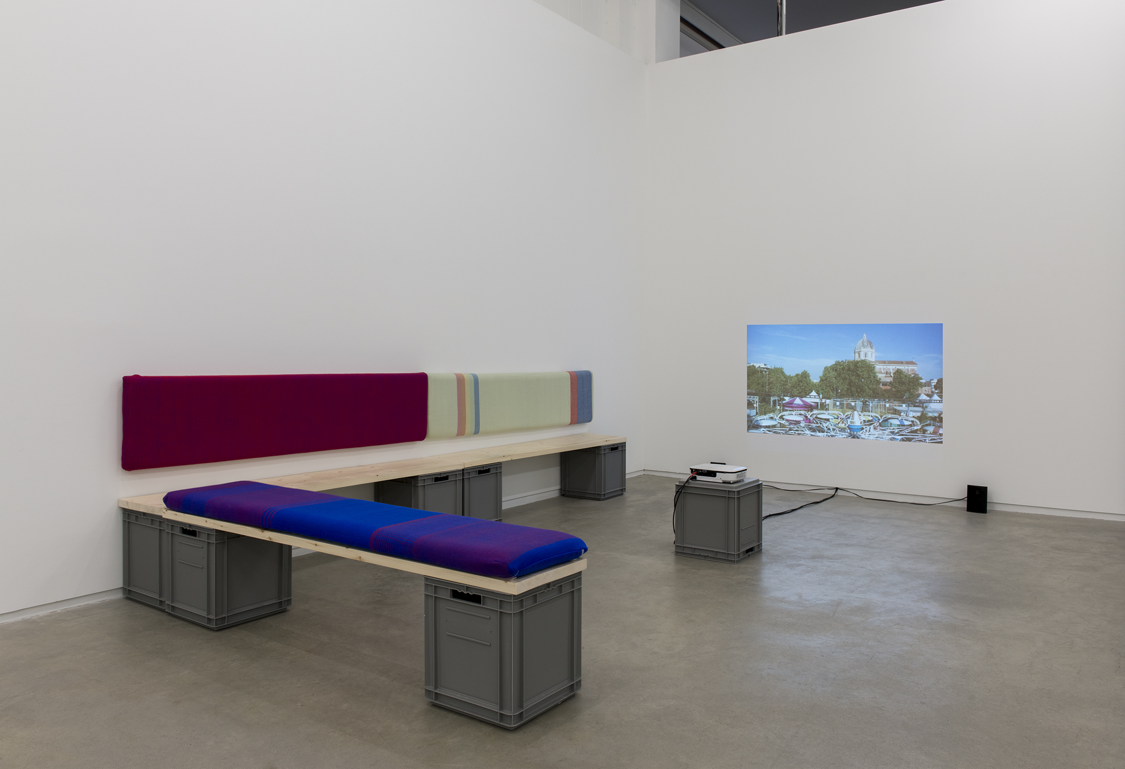 Andrea Büttner, Benches, 2013, handwoven wool backrests, spruce, plastic crates, each 37 x 78 x 16 in. (93 x 2 x 40 cm), Little sisters, Lunapark, Ostia, 2012, HDV, dimensions variable by