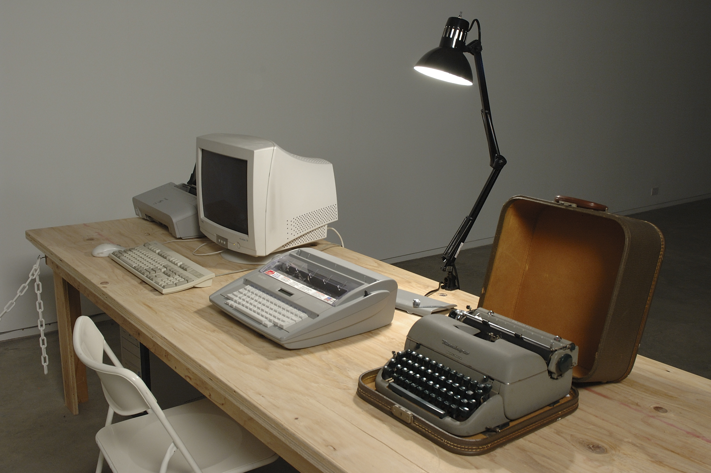 Isabelle Pauwels, Untitled, 2006, remington manual typewriter, brother sx-4000 electronic typewriter, CPU, monitor, printer, white office chair, shelf, lamp, time cards, filing tray, office supplies, galley slave edition poster, dimensions variable by