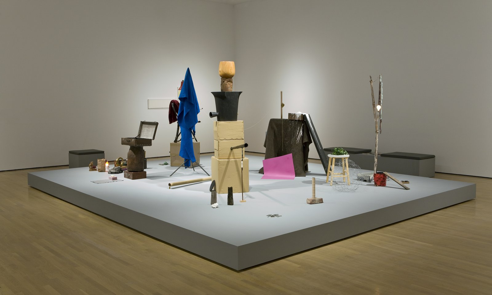 Geoffrey Farmer,And Finally the Street Becomes the Main Character (Clock), 2005–2008, wooden stage, computer controlled soundscape, 8 speakers, styrene brick, glass shards, paint can, tree branch, paint tray, stool, artificial ivy, hand carved wooden bowl, cardboard boxes, wooden mallet, protest sign, cardboard tubes, leather suitcase, folding chair, towel, sweater, desk lamp, string, blanket, light bulbs, tripod, sponge, lock box, tissue, paper bag, oil can, moth, thread, masking tape, felt, books, rag, wooden figure, spoon, paint, styrene cup, chopstick, candleholder, ballet costume, brass sculpture, found wood, various framed works, dimensions variable