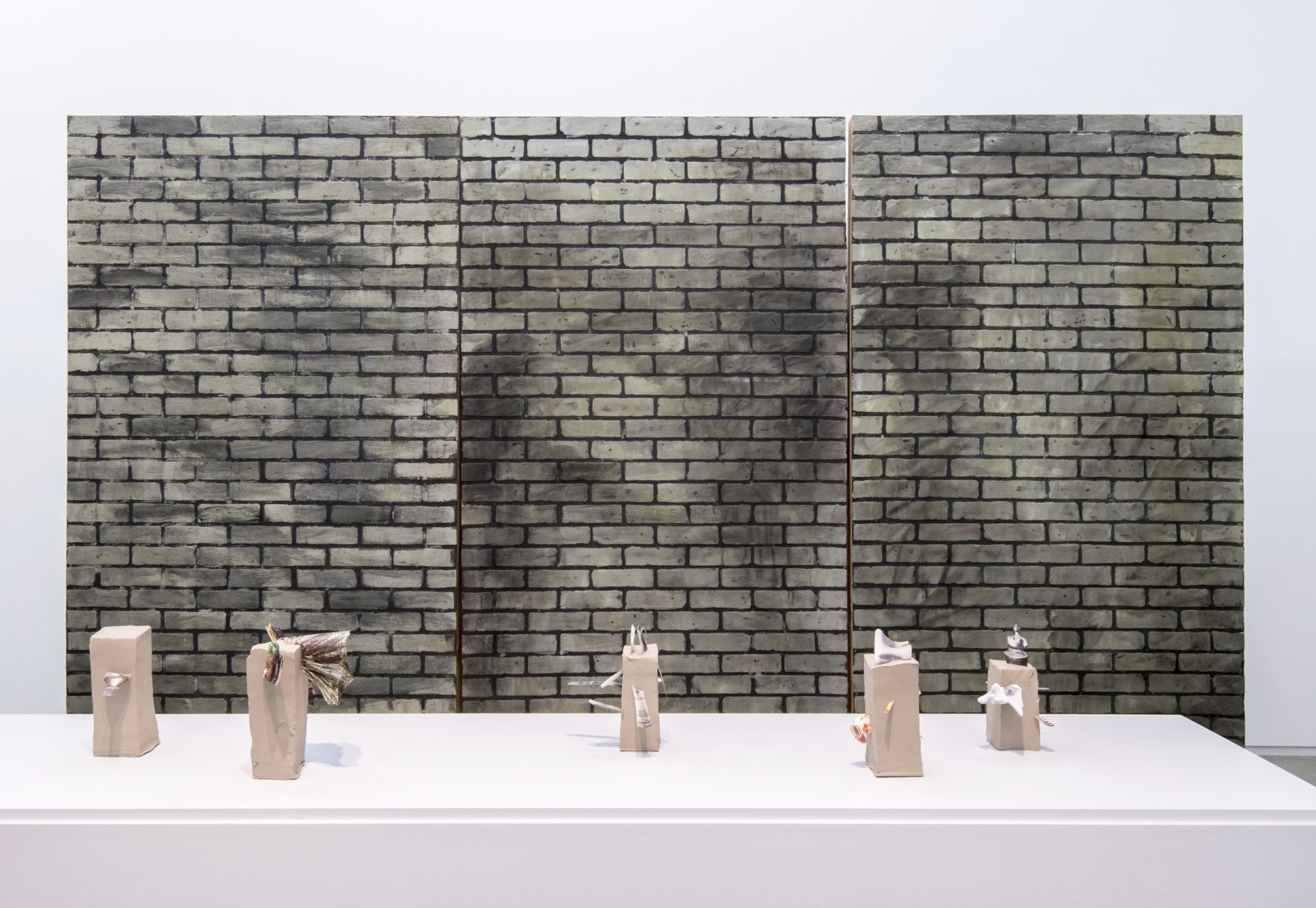 Geoffrey Farmer,Archaeology with Looking at a photograph of myself and realizing I had a potato instead of a head (Fountain)(detail), 2014, vitrine with cut-outs mounted on 5 vertical clay slabs, 4 wooden wall brick façades, paint, sandbags, framed cut-outs and ink mounted on paper, dimensions variable