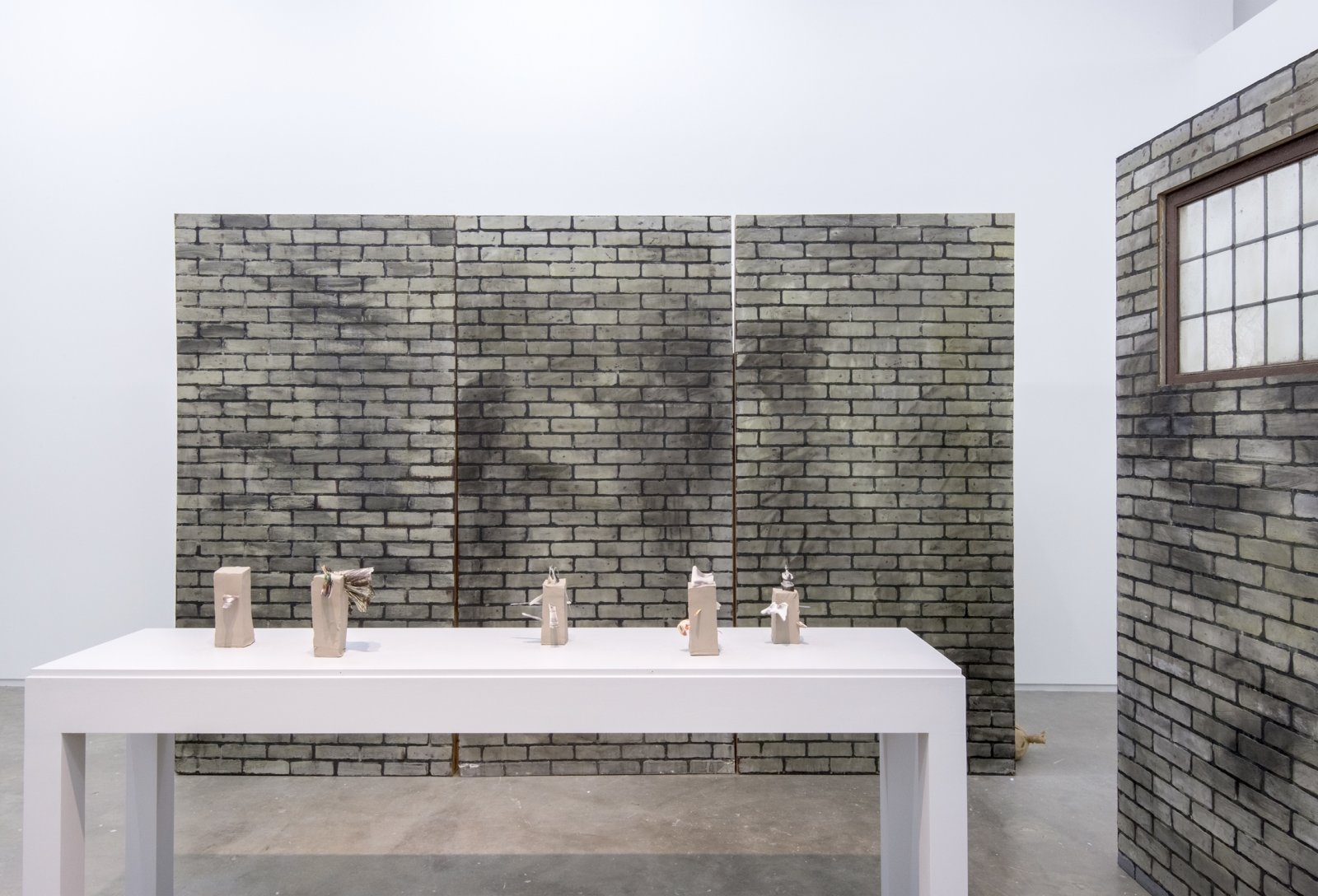 Geoffrey Farmer,ArchaeologywithLooking at a photograph of myself and realizing I had a potato instead of a head (Fountain)(detail), 2014, vitrine with cut-outs mounted on 5 vertical clay slabs, 4 wooden wall brick façades, paint, sandbags, framed cut-outs and ink mounted on paper, dimensions variable