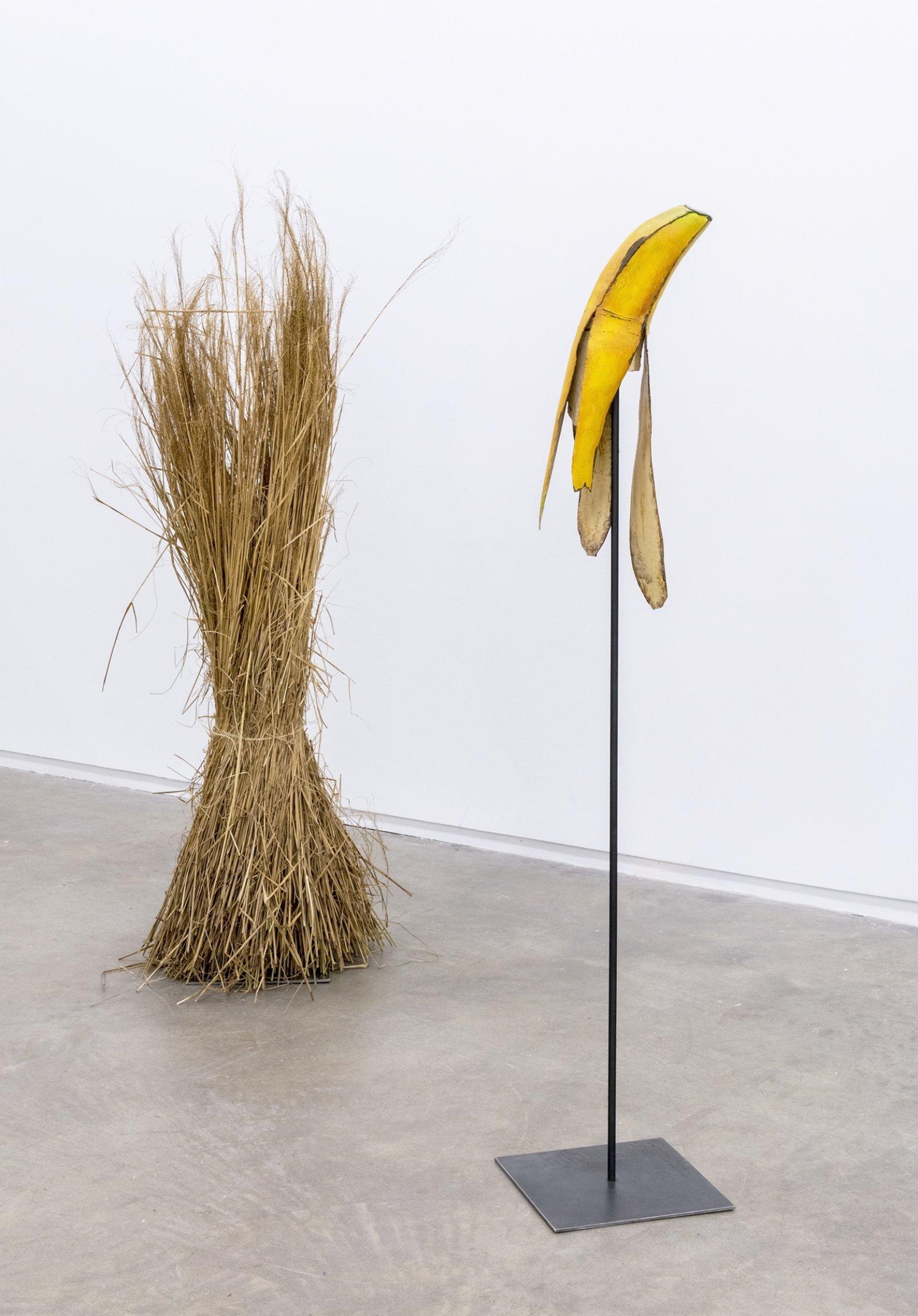 Geoffrey Farmer, Banana and Grass, 2014, paint, foam, grass, metal stand, 2 wooden wall façades, window, sandbags, banana: 67 x 12 x 12 in. (170 x 31 x 31 cm), grass: 76 x 21 x 21 in. (193 x 54 x 54 cm)