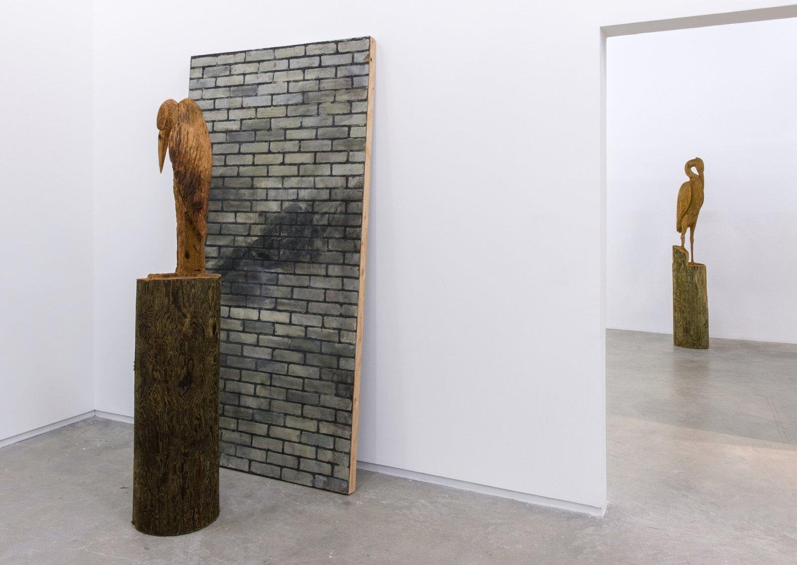 Geoffrey Farmer, Good And Evil, 2014, decommissioned cedar telephone poles, chainsaw carving by Brigitte Lochhead, wooden wall brick façade, Good: 77 x 15 x 14 in. (196 x 38 x 36 cm), Evil: 82 x 14 x 13 in. (208 x 36 x 33 cm) by Geoffrey Farmer