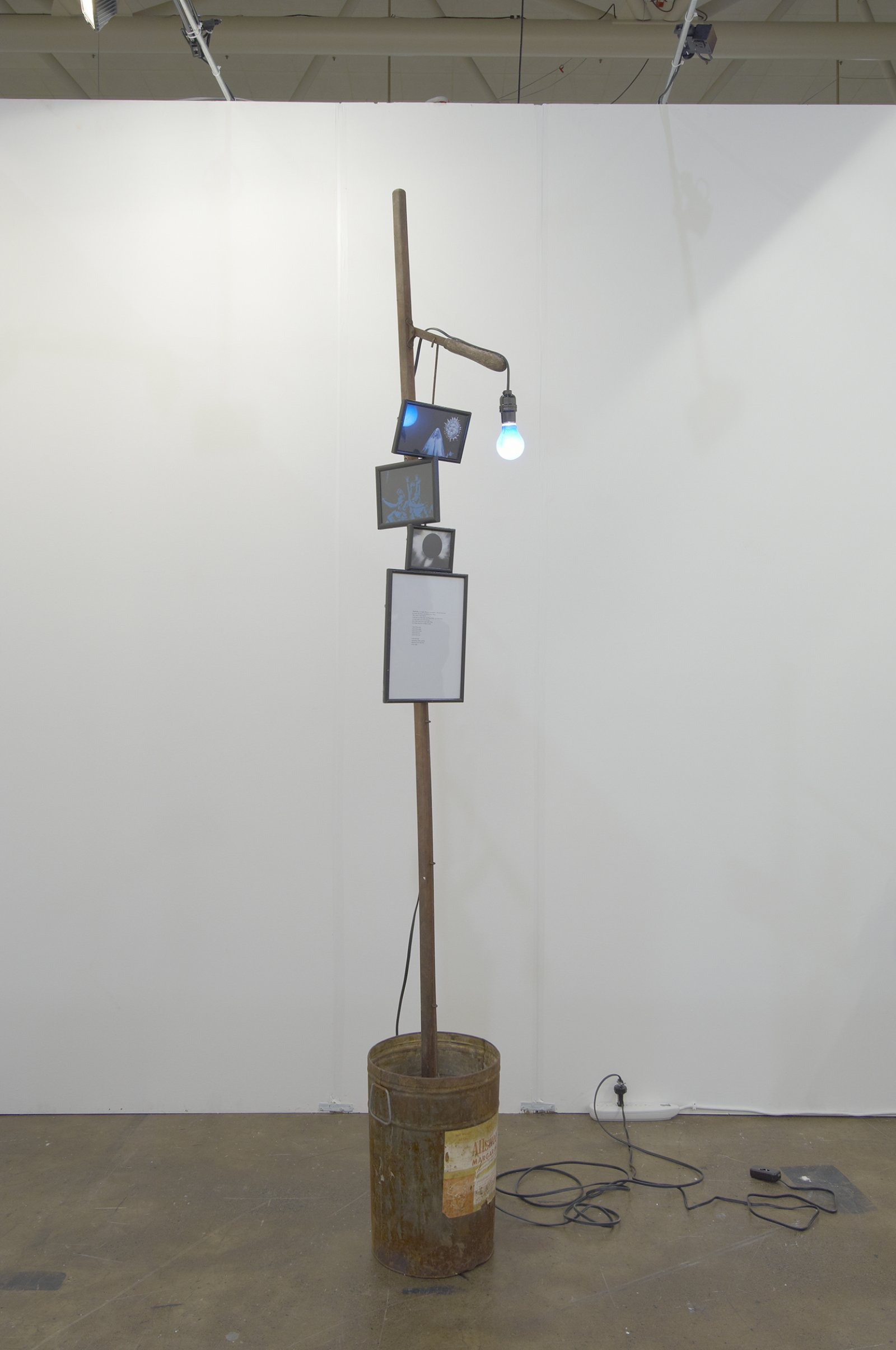 Geoffrey Farmer,I am by nature one and also many, dividing the single me into many, and even opposing them as great and small, light and dark, and in ten thousand other ways, 2006–2008,pruning pole, margarine bucket, concrete, poem, framed pictures, bluelight, 97 x 18 x 12 in. (246 x 46 x 31 cm)