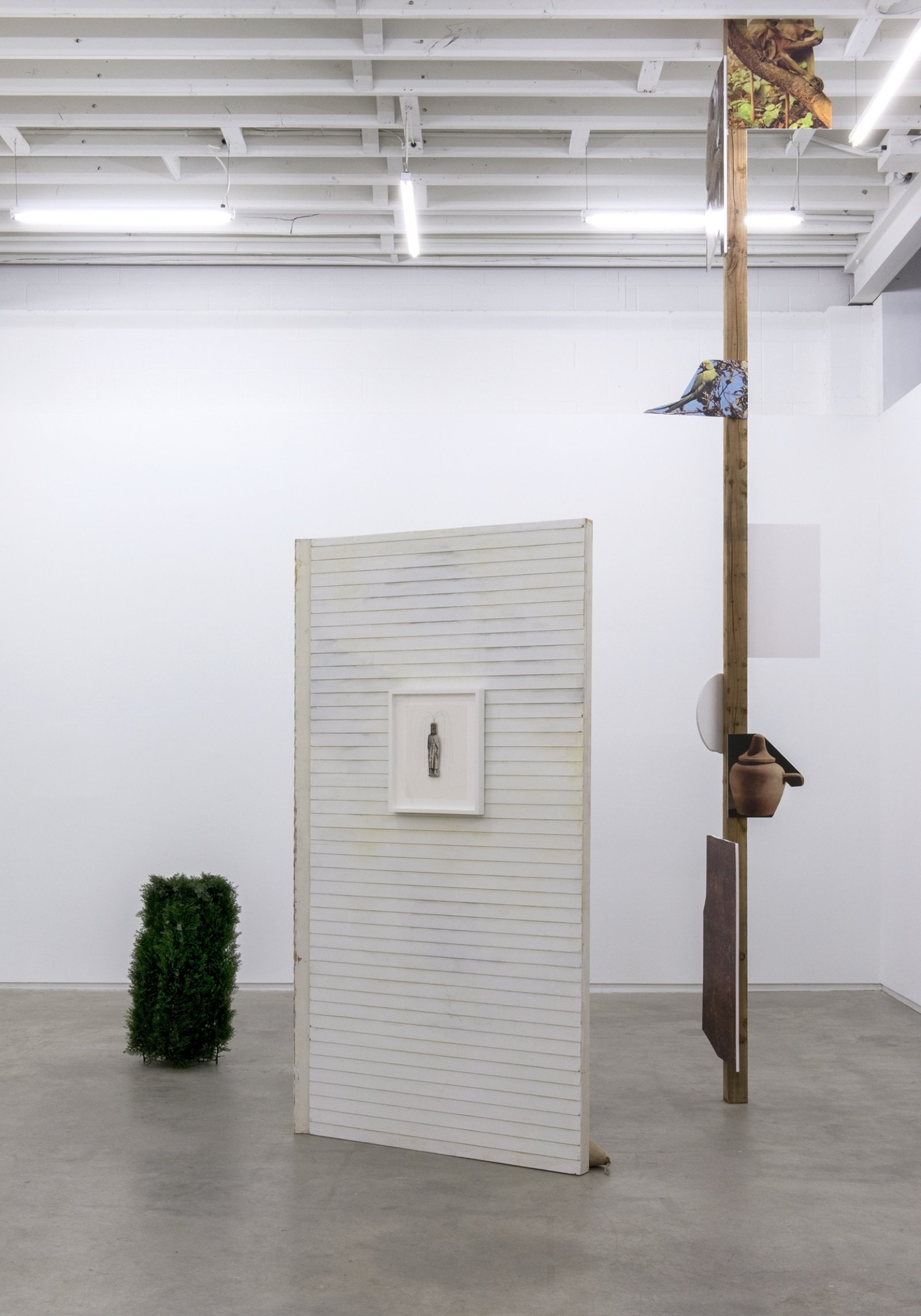Geoffrey Farmer, This is where the plate goes..., 2014, douglas fir pole, 7 photographs mounted on foamcore, plastic topiary, 2 wooden wall façades, paint, window, sandbags, framed ink and cut-outs mounted on paper, dimensions variable by Geoffrey Farmer