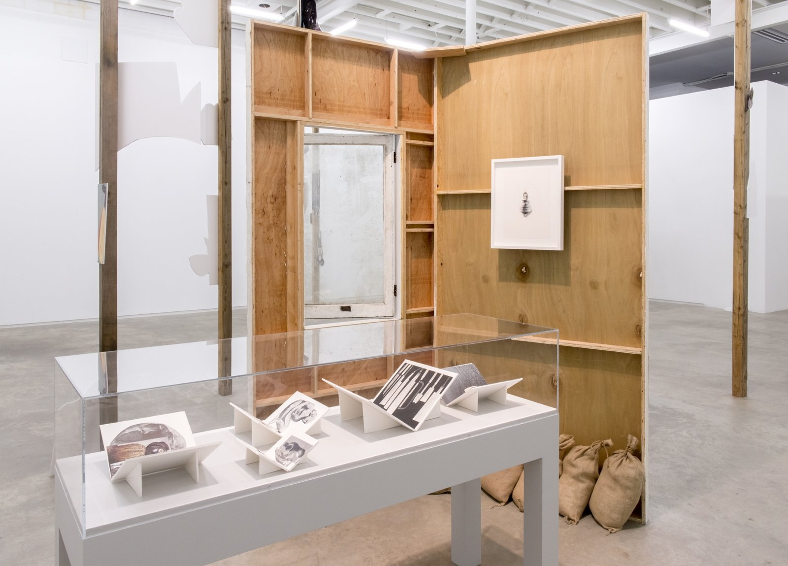 Geoffrey Farmer,Workbooks with When I got fired from that Beckett Play (Fountain)(detail),2014, vitrine with 5 cut-outs collaged on foamcore, 2 wooden wall façades, paint, window, sandbags, framed cut-outs and ink mounted on paper, dimensions variable