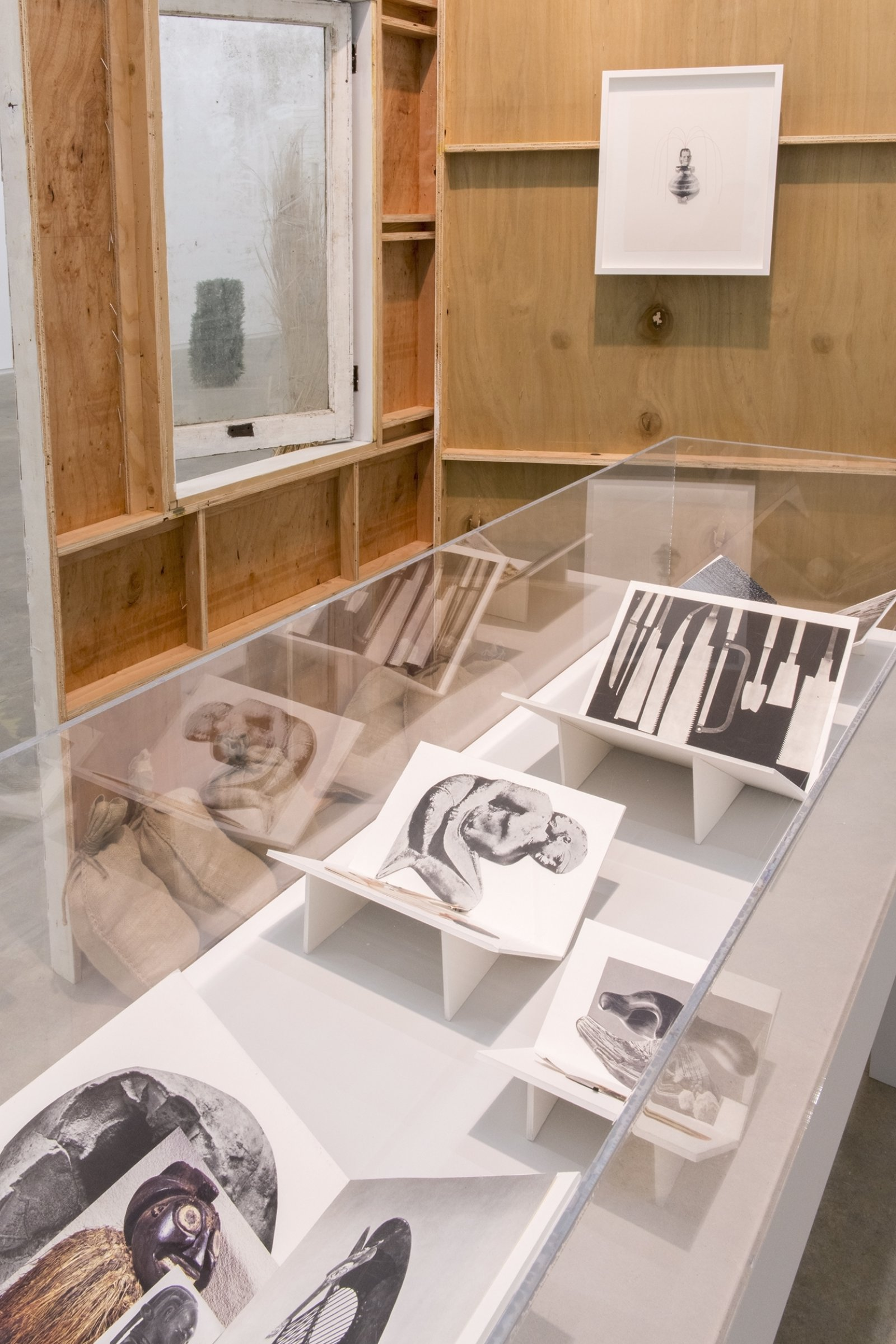 Geoffrey Farmer,Workbookswith When I got fired from that Beckett Play (Fountain)(detail),2014, vitrine with 5 cut-outs collaged on foamcore, 2 wooden wall façades, paint, window, sandbags, framed cut-outs and ink mounted on paper, dimensions variable