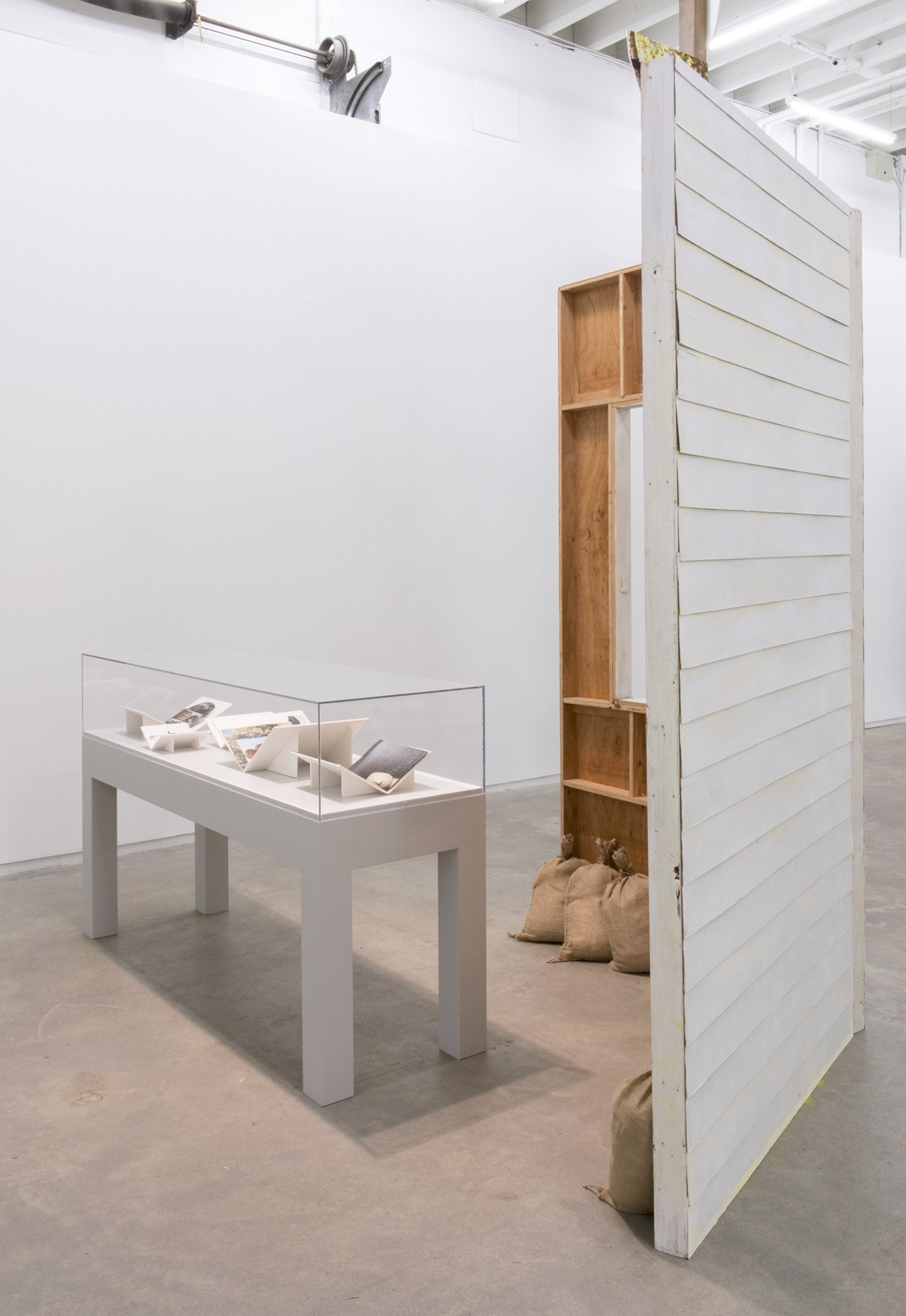 Geoffrey Farmer,Workbookswith When I got fired from that Beckett Play (Fountain),2014, vitrine with 5 cut-outs collaged on foamcore, 2 wooden wall façades, paint, window, sandbags, framed cut-outs and ink mounted on paper, dimensions variable