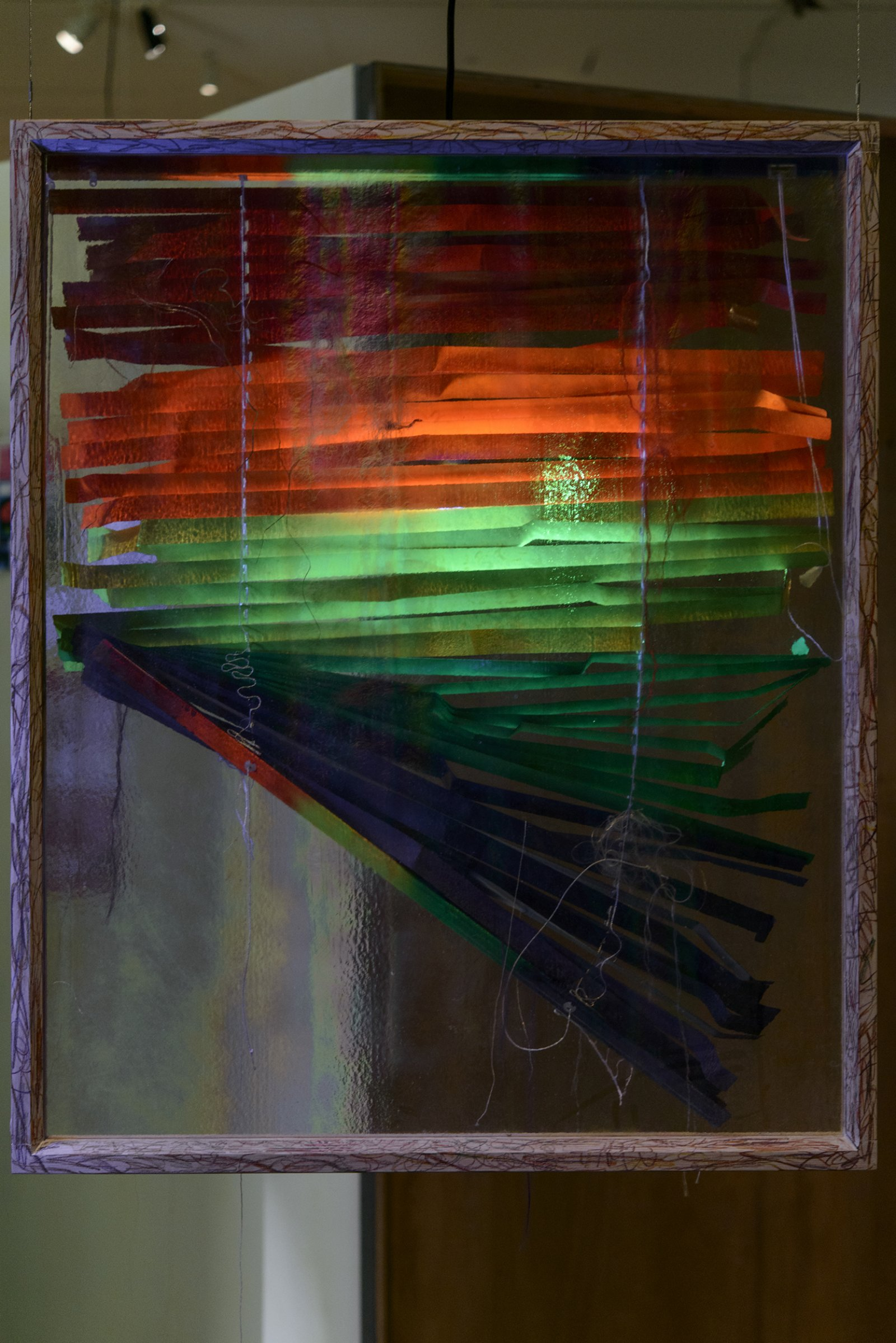 Julia Feyrer,Blinded/Braided, 2013, venetian blind, human hair, corn hair, wig hair, milk wash wood frame with rainbow crayon, dimensions variable. Installation view,The Intellection of Lady Spider House, Art Gallery of Alberta, 2013.