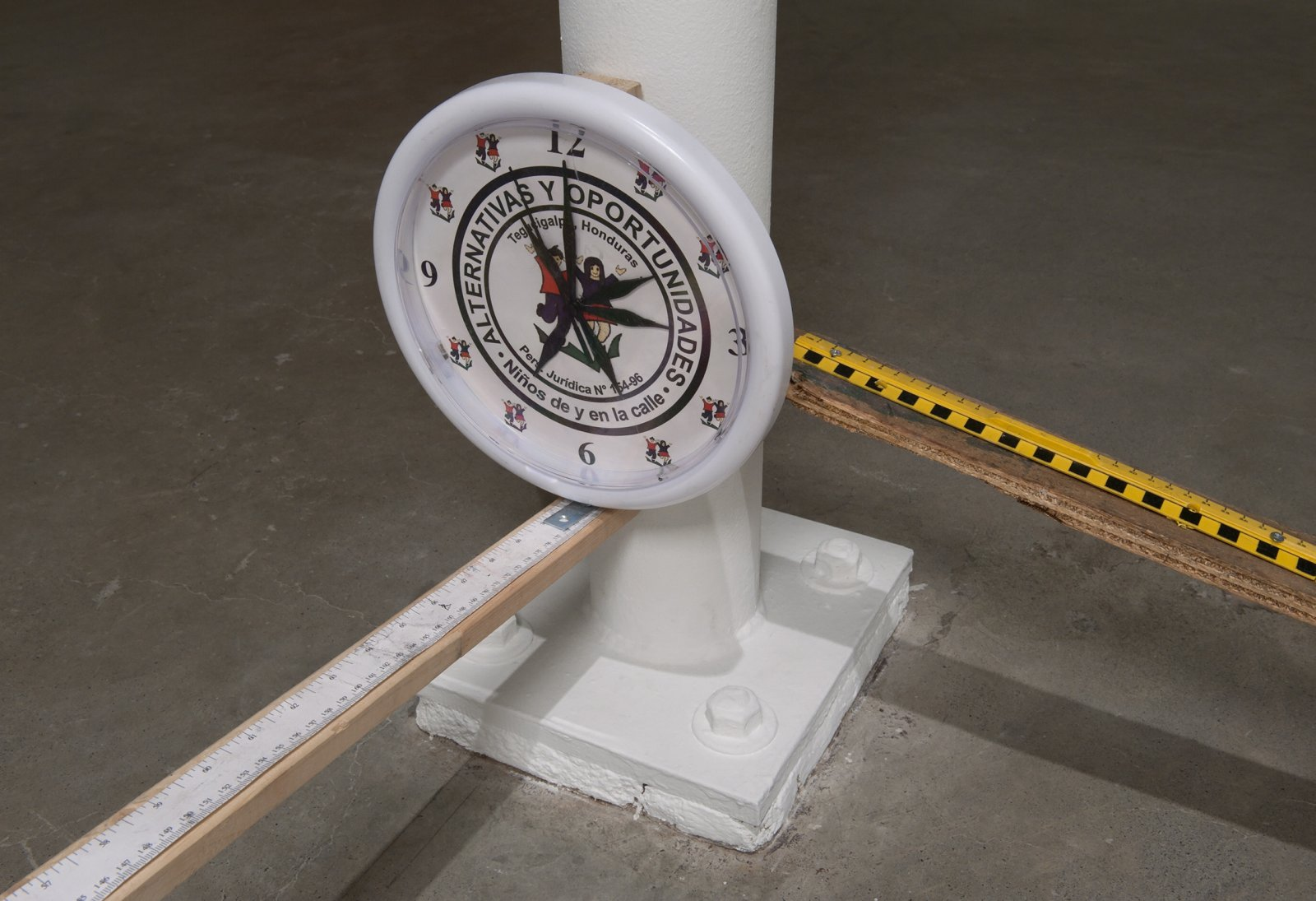 Julia Feyrer, Canada Arm & Honduras Clock (detail), 2012, Canadian Study of Diet Lifestyle and Health paper, tape measure, Alternativas y Oportunidades souvenir clock from Tegucigalpa, Honduras, wood, handle, camera mount by Julia Feyrer