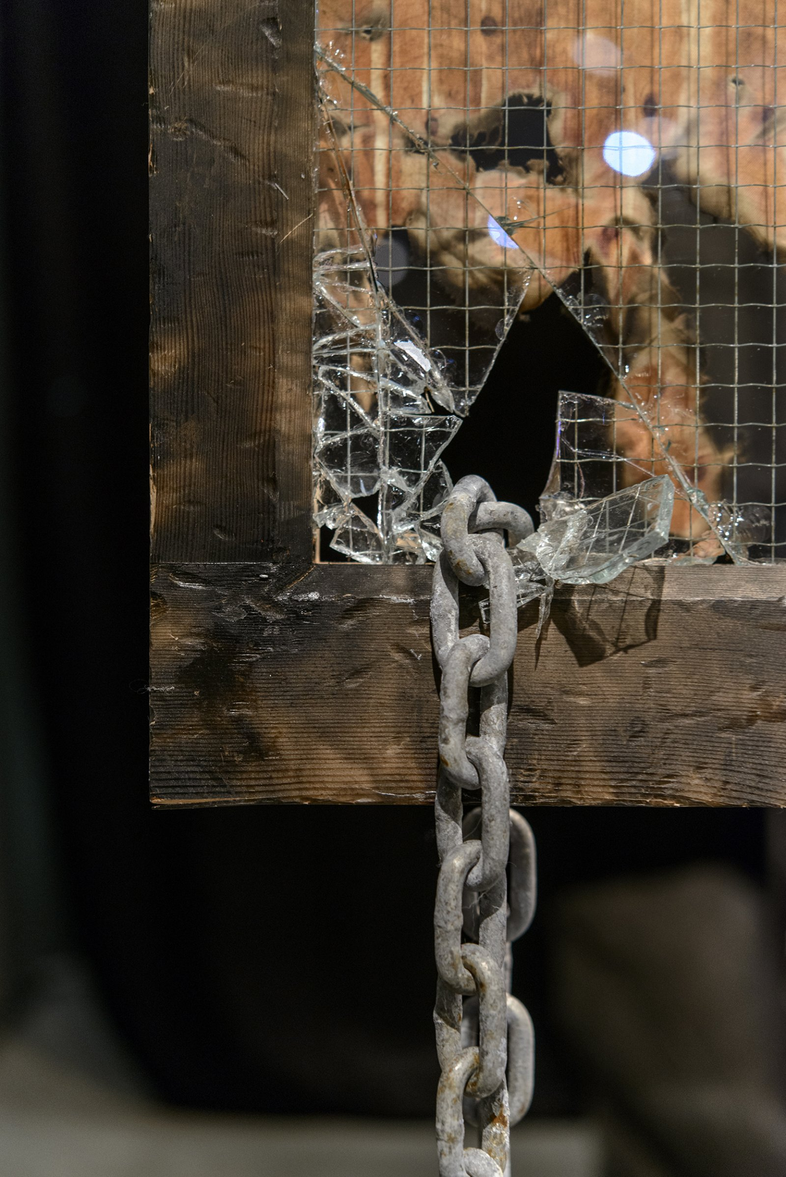 Julia Feyrer,Chained/Charred, 2013, burnt fabric, corroded chain, security glass, hand painted sign, charcoaled wood frame, dimensions variable. Installation view,The Intellection of Lady Spider House, Art Gallery of Alberta, 2013.