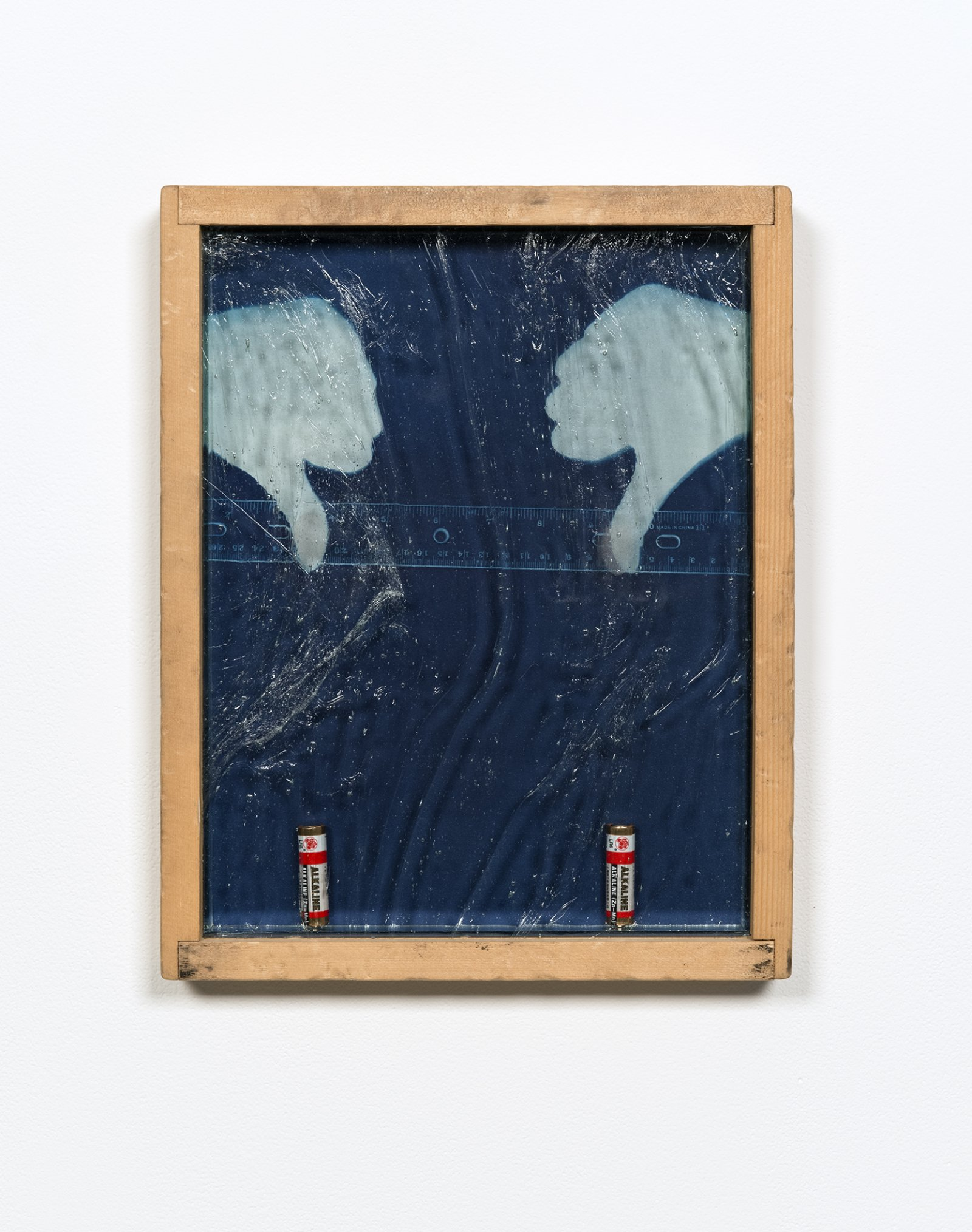 "Julia Feyrer, Rule of thumbs: Double Negative, 2012, antiqued/distressed pine wood frame (beaten with chain, orange pekoe stain), cyanotype on watercolour paper, two dead aa alkaline batteries, magnets, mirror inset, ""alte deutsch"" architectural glass, thumb fingerprints dusted with bi-chromatic fingerprint powder, 15 x 12 in. (39 x 30 cm)"