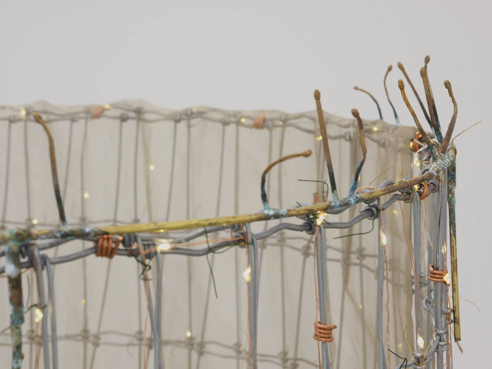 Rochelle Goldberg, Trigger: Towards everything they've ever wanted (detail), 2019, ranch fencing, batteries, fairy lights, polyester curtain, aluminum, cast bronze matches, copper wire, 51 x 51 x 44 in. (130 x 130 x 112 cm) by Rochelle Goldberg