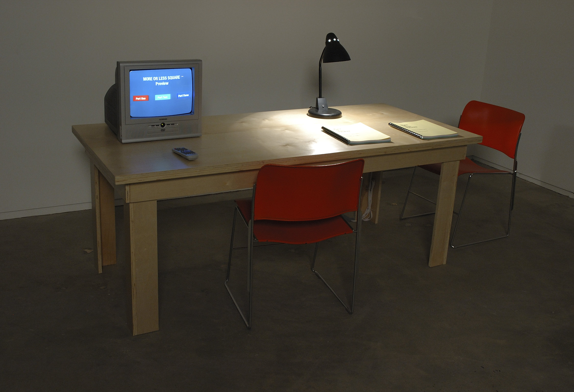 Isabelle Pauwels, Untitled, 2006, curtis combination DVD player, monitor with remote control, introductions DVD, table, 2 copies of More or Less Square: A Book in Three Parts, lamp​​, dimensions variable by