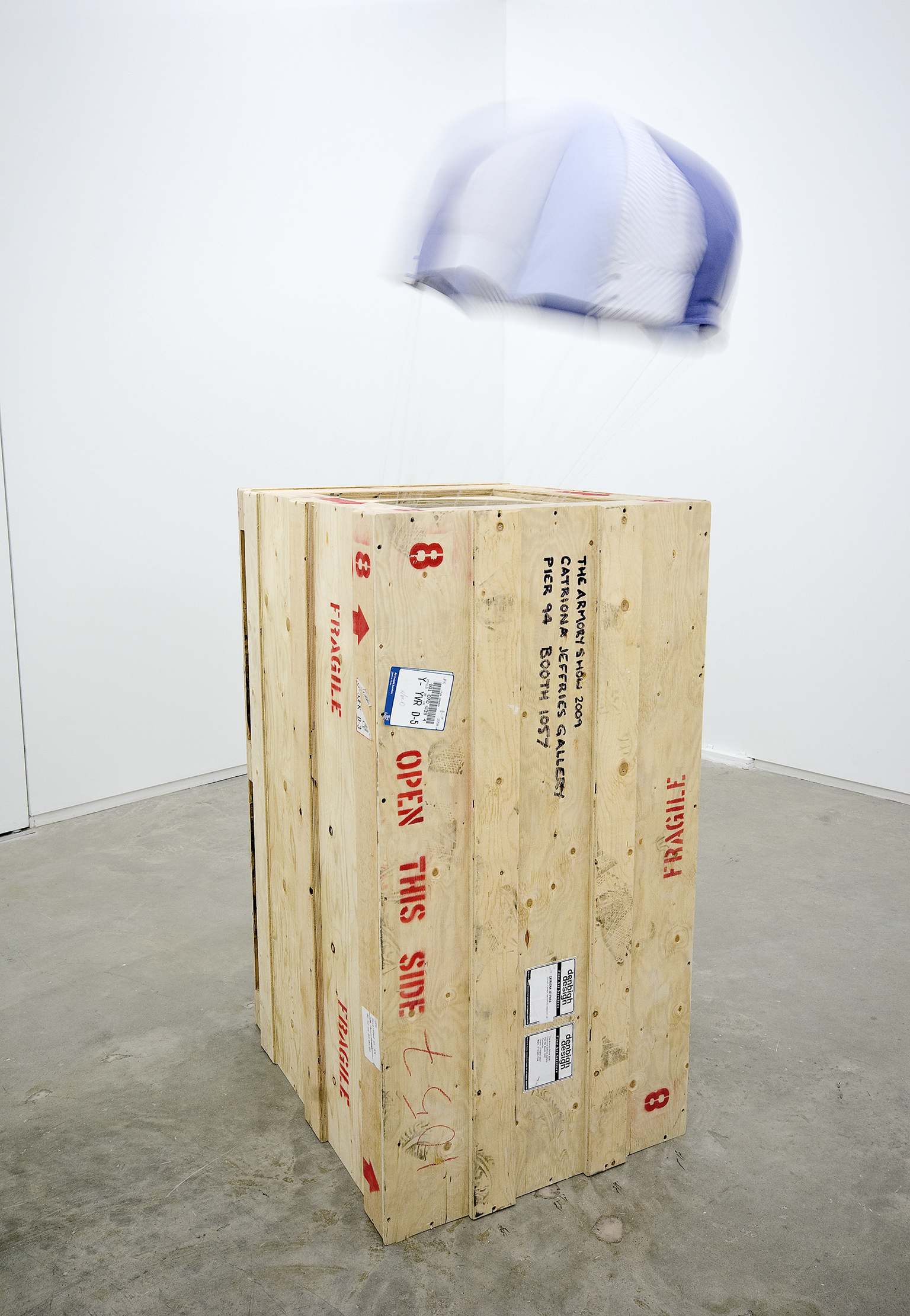 Brian Jungen, Falling Crate, 2009, shirts, Navajo wool, electric fan, plywood crate, 88 x 36 x 29 in. (224 x 91 x 72 cm) by