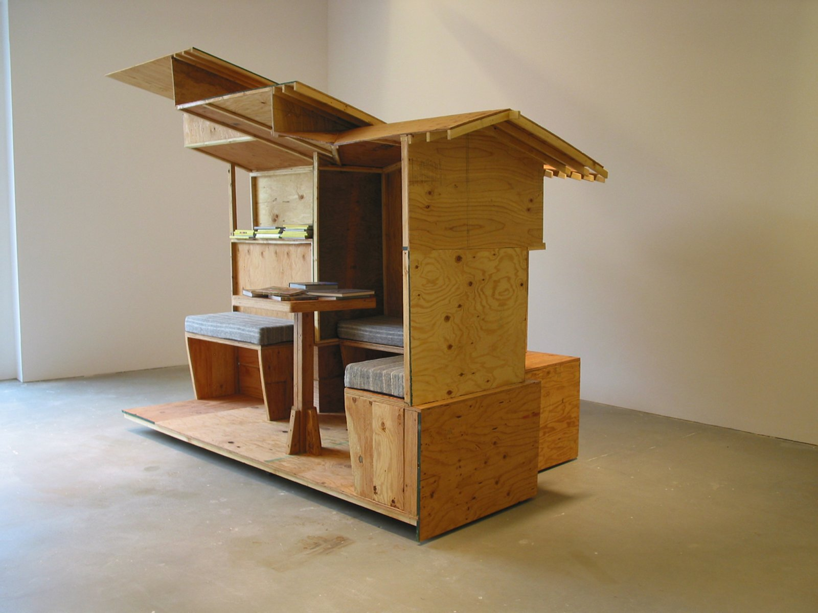Brian Jungen,Arts and Crafts Book Depository / CappStreet Project 2004, 2004,architectural model (scale of Greene and Greene's Gamble House) made of plywood sectioned into 4 quadrants, locking castors, bookshelves, 2 framed glass cabinets with electrical source and lighting unit, hand-made fabric pillows for seating benches, video monitor, ongoing accumulation of library inventory of magazines, journals, books and videos, 108 x 192 x 252 in. (274 x 488 x 640 cm)