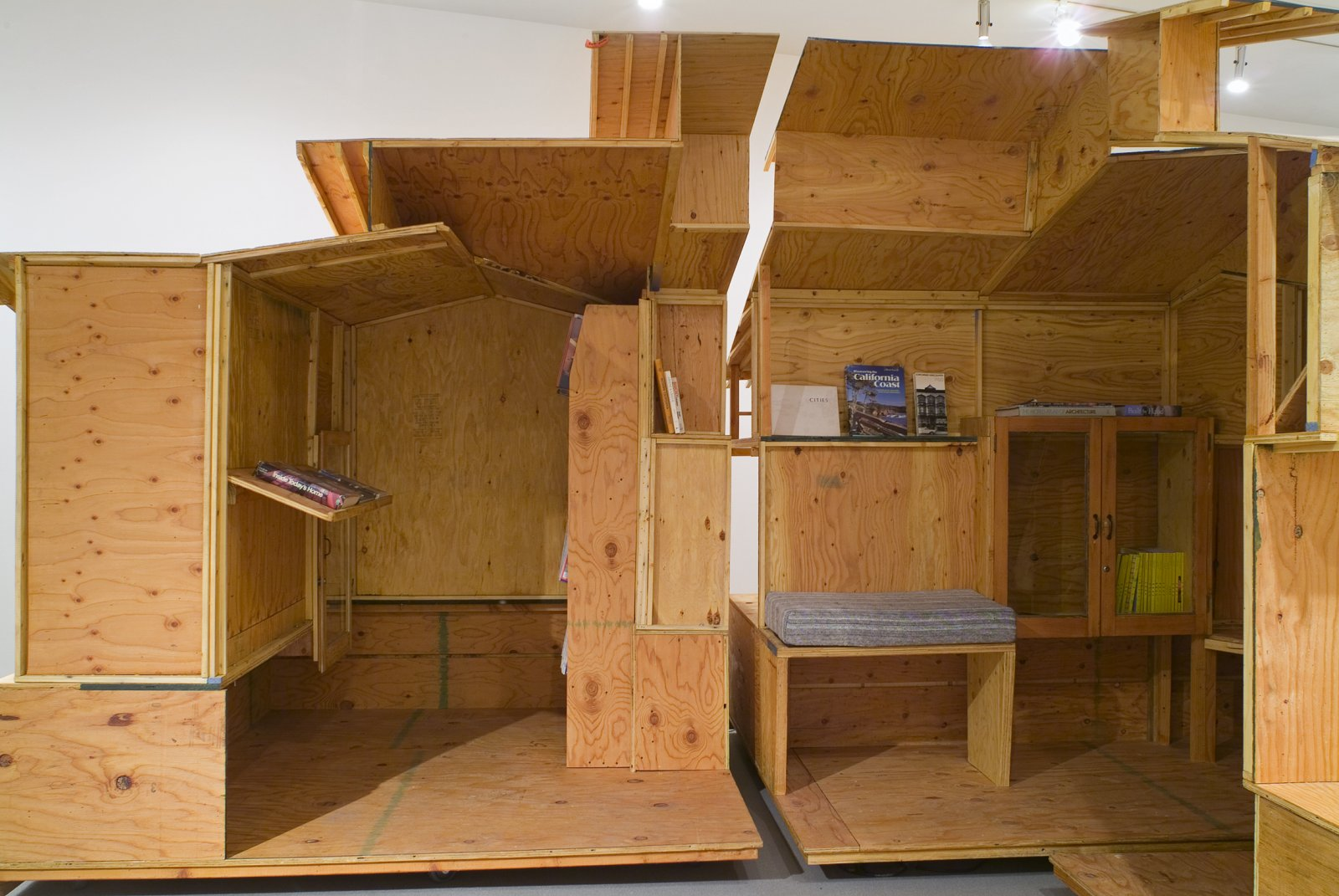 Brian Jungen,Arts and Crafts Book Depository / CappStreet Project 2004(detail), 2004,architectural model (scale of Greene and Greene's Gamble House) made of plywood sectioned into 4 quadrants, locking castors, bookshelves, 2 framed glass cabinets with electrical source and lighting unit, hand-made fabric pillows for seating benches, video monitor, ongoing accumulation of library inventory of magazines, journals, books and videos, 108 x 192 x 252 in. (274 x 488 x 640 cm)
