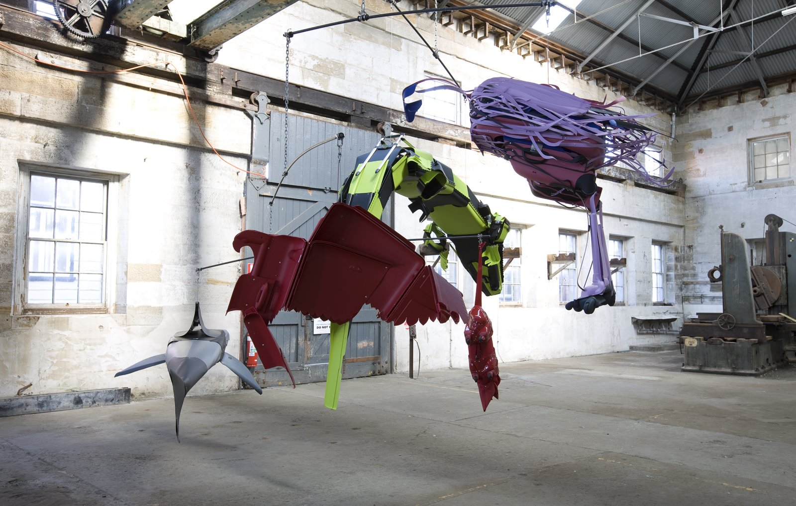 Brian Jungen,Crux (as seen from those who sleep on the surface of the earth under thenight sky), 2008,suspended mobile of steel, cut up travel suitcases, rowboat with oars installed on ground, dimensions variable. Installation view,SydneyBiennale,Sydney,Australia, 2008