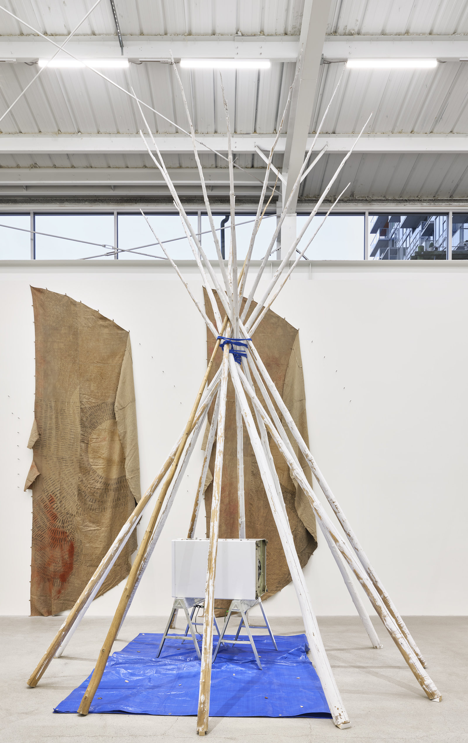 Duane Linklater, anteclovis, 2020, teepee poles, paint, nylon rope, tarpaulin, steel sawhorses, washing machine, tie-down strap, arrowheads, 230 x 158 x 158 in. (584 x 401 x 401 cm)