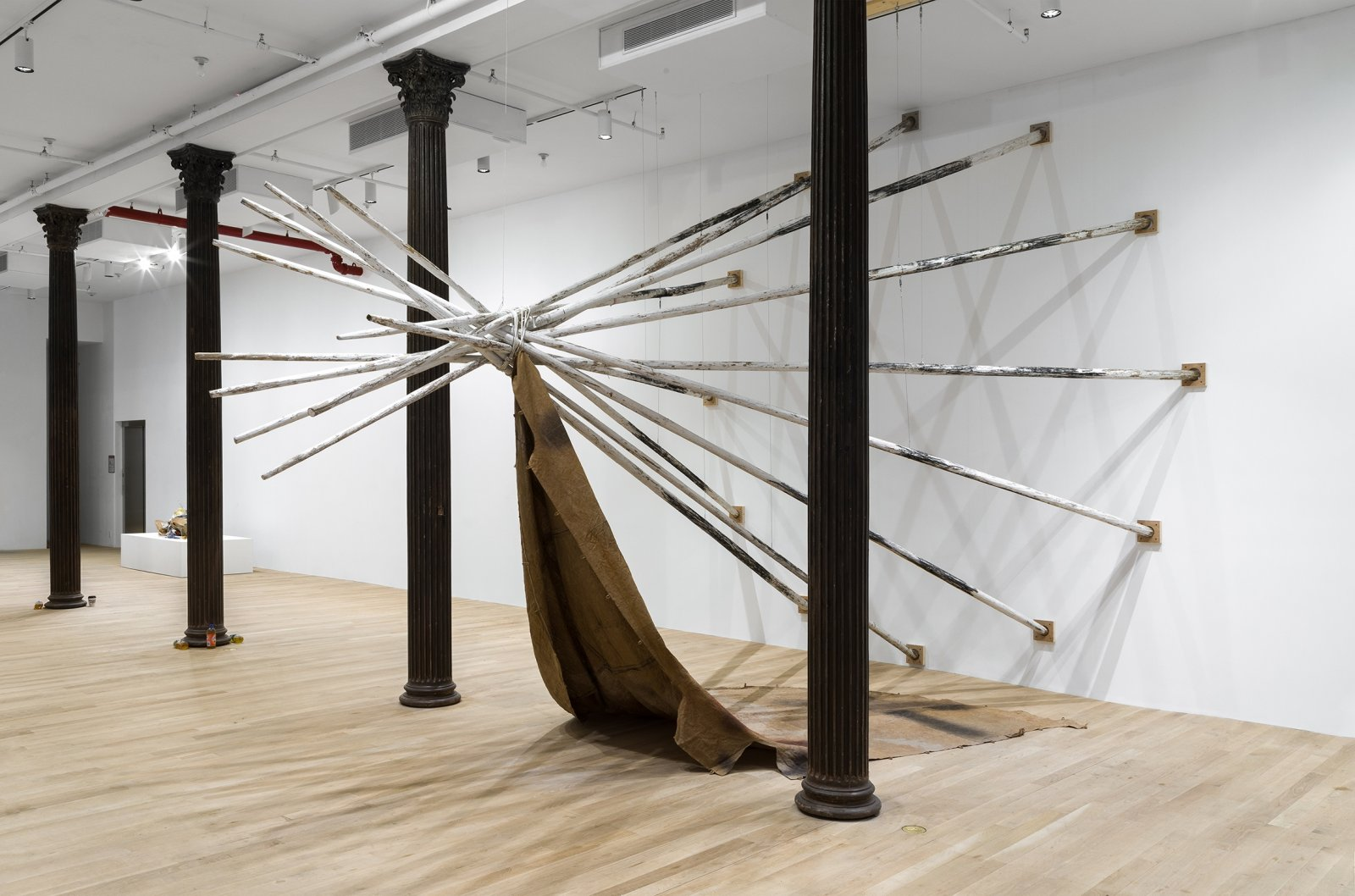 Duane Linklater, dislodgevanishskinground, 2019, 12 teepee poles, steel cable, white paint, charcoal, rope, digital print on linen, black tea, blueberry extract, sumac, charcoal, 220 x 174 x 174 in. (559 x 442 x 442 cm). Installation view, Artists Space, New York, USA, 2019