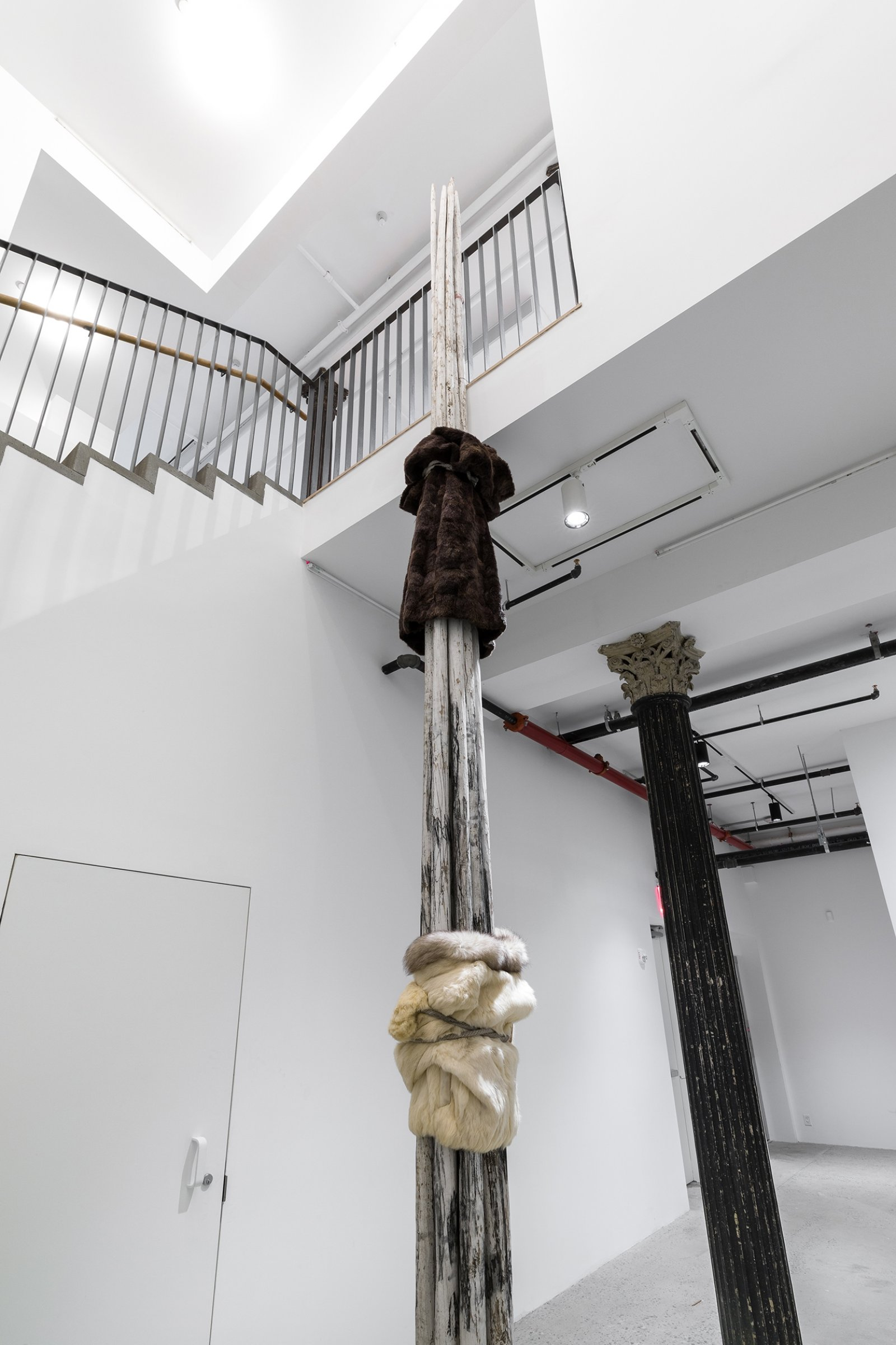 Duane Linklater, landlesscolumnbundle (detail), 2019, teepee poles, white paint, charcoal, rabbit fur coat, mink fur coat, rope, 243 x 10 x 10 in. (617 x 25 x 25 cm). Installation view, Artists Space, New York, USA, 2019