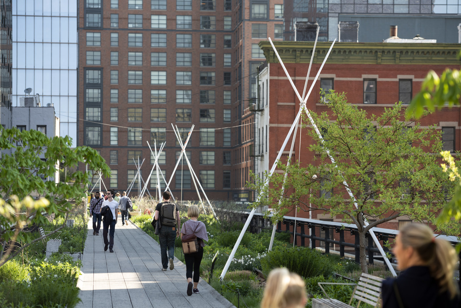 Duane Linklater, pêyakotênaw, 2018, teepee poles, rope, stones, flagging tape, paint, each approximately 181 x 143 x 143 in. (456 x 363 x 363 cm). Installation view, Agora, High Line Art, New York, 2018