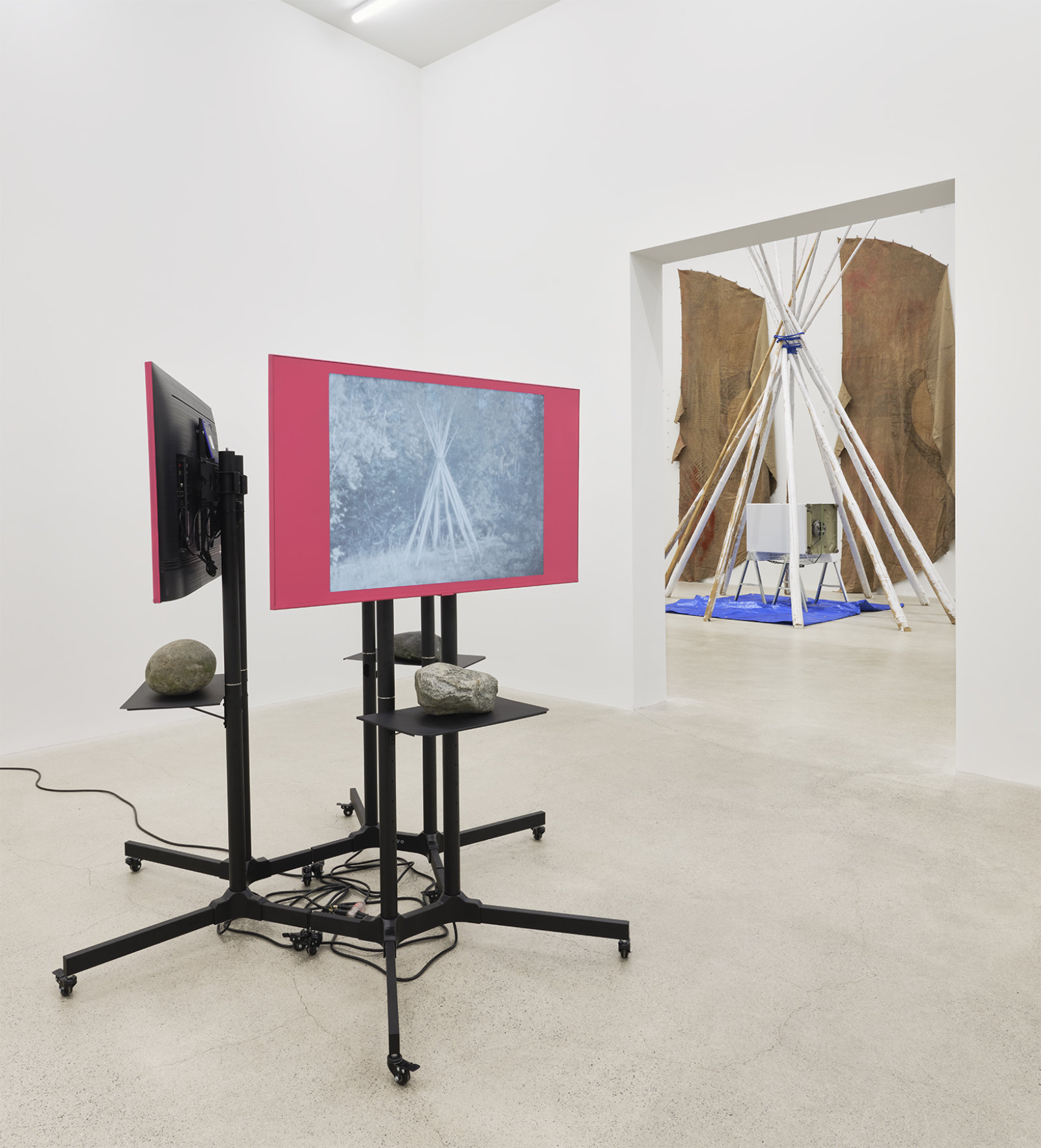 Duane Linklater, primaryuse, 2020, lcd screens, television stands, media players, spray paint, stones, 3 super 8mm film transfers to 2k video with audio, score by eagles with eyes closed, looping: 5 minutes, 19 seconds; 5 minutes, 10 seconds; 5 minutes, 23 seconds; 69 x 72 x 72 in. (175 x 183 x 183 cm)