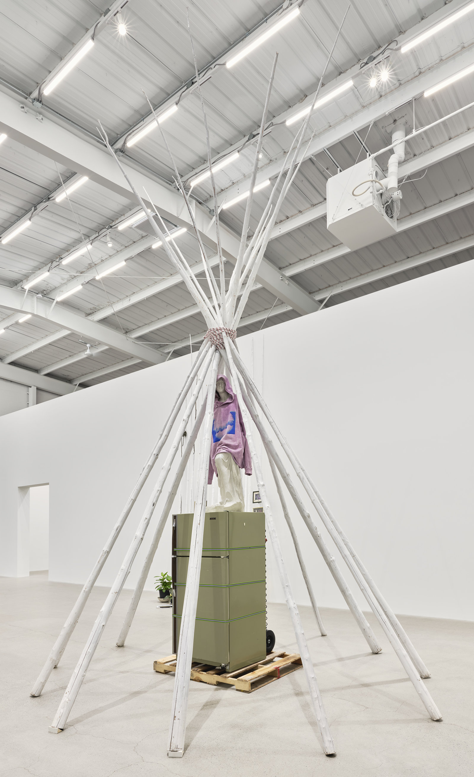 Duane Linklater, what grief conjures, 2020, teepee poles, paint, nylon rope, wooden pallet, refrigerator, tie-down straps, hand truck, plastic statue, handmade hoodie, cochineal dye, silkscreen, 249 x 160 x 160 in. (632 x 406 x 406 cm) by Duane Linklater