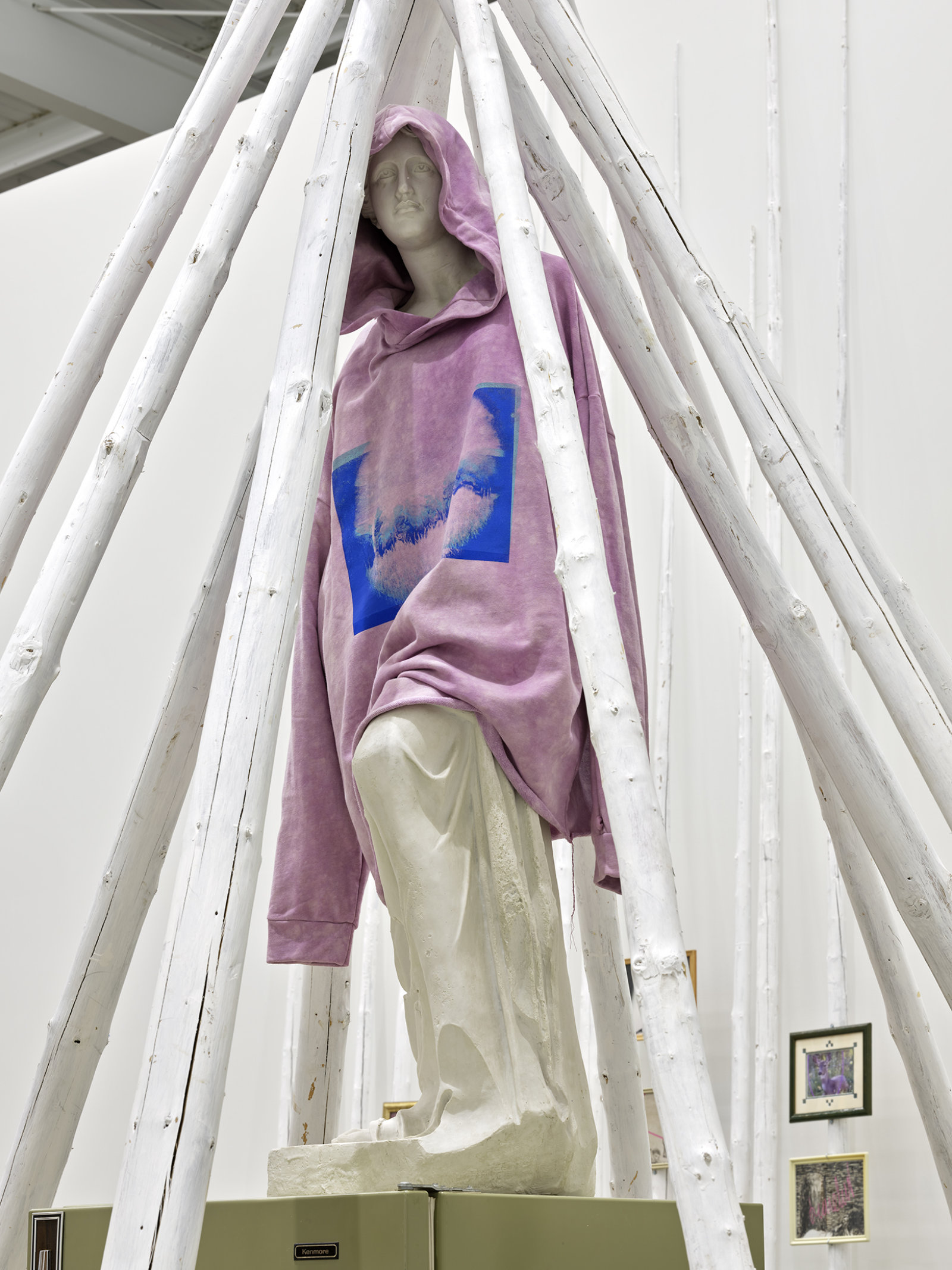 Duane Linklater, what grief conjures (detail), 2020, teepee poles, paint, nylon rope, wooden pallet, refrigerator, tie-down straps, hand truck, plastic statue, handmade hoodie, cochineal dye, silkscreen, 249 x 160 x 160 in. (632 x 406 x 406 cm) by Duane Linklater