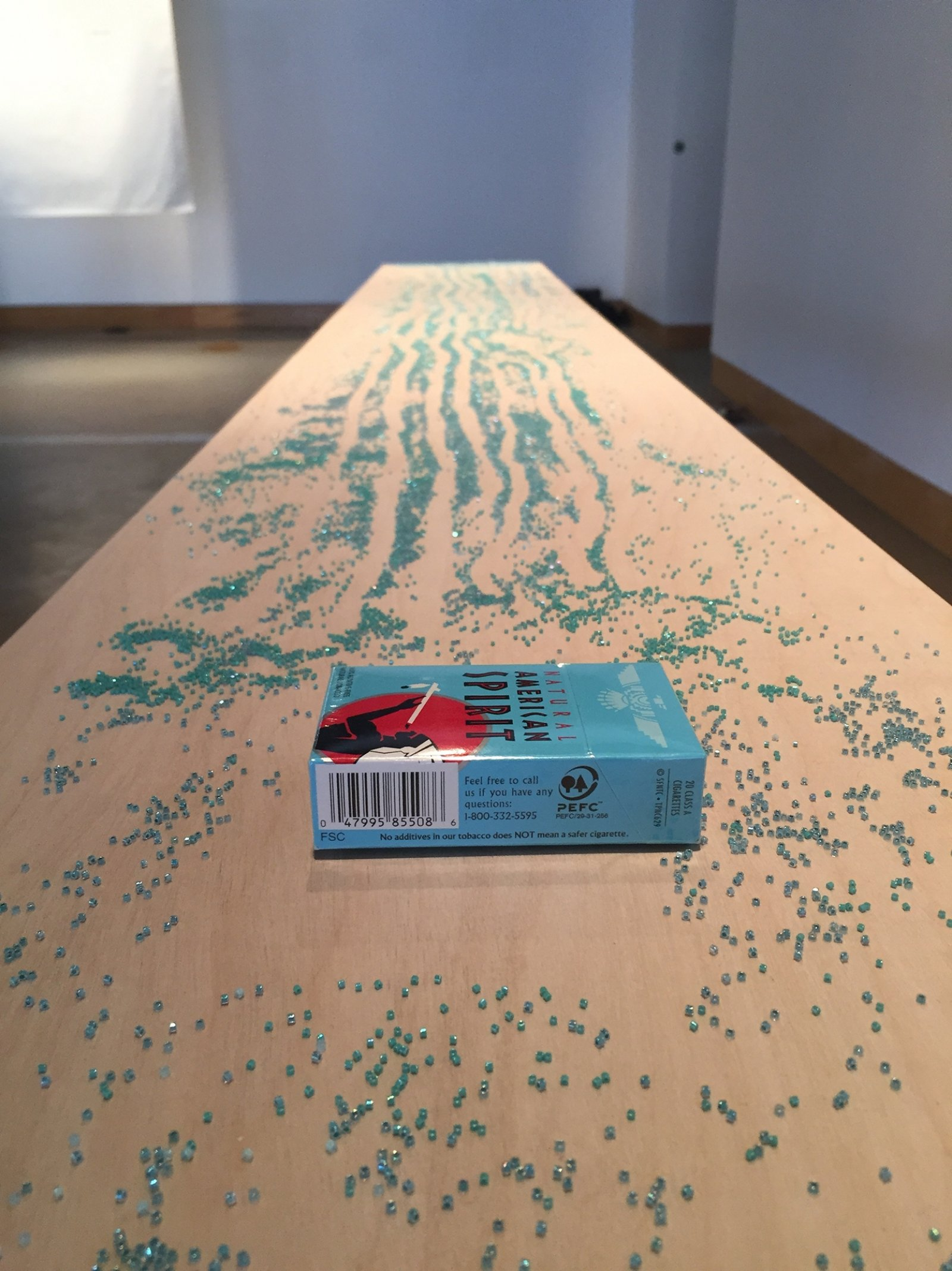 Tanya Lukin Linklater, Slow Scrape and the Harvest Sturdies, 2015–2017, tables, beads, American Spirit cigarettes, crushed charcoal, each table 29 x 96 x 13 in. (74 x 244 x 33 cm). Installation view, The Harvest Sturdies, All My Relations Arts, Minneapolis, USA, 2017