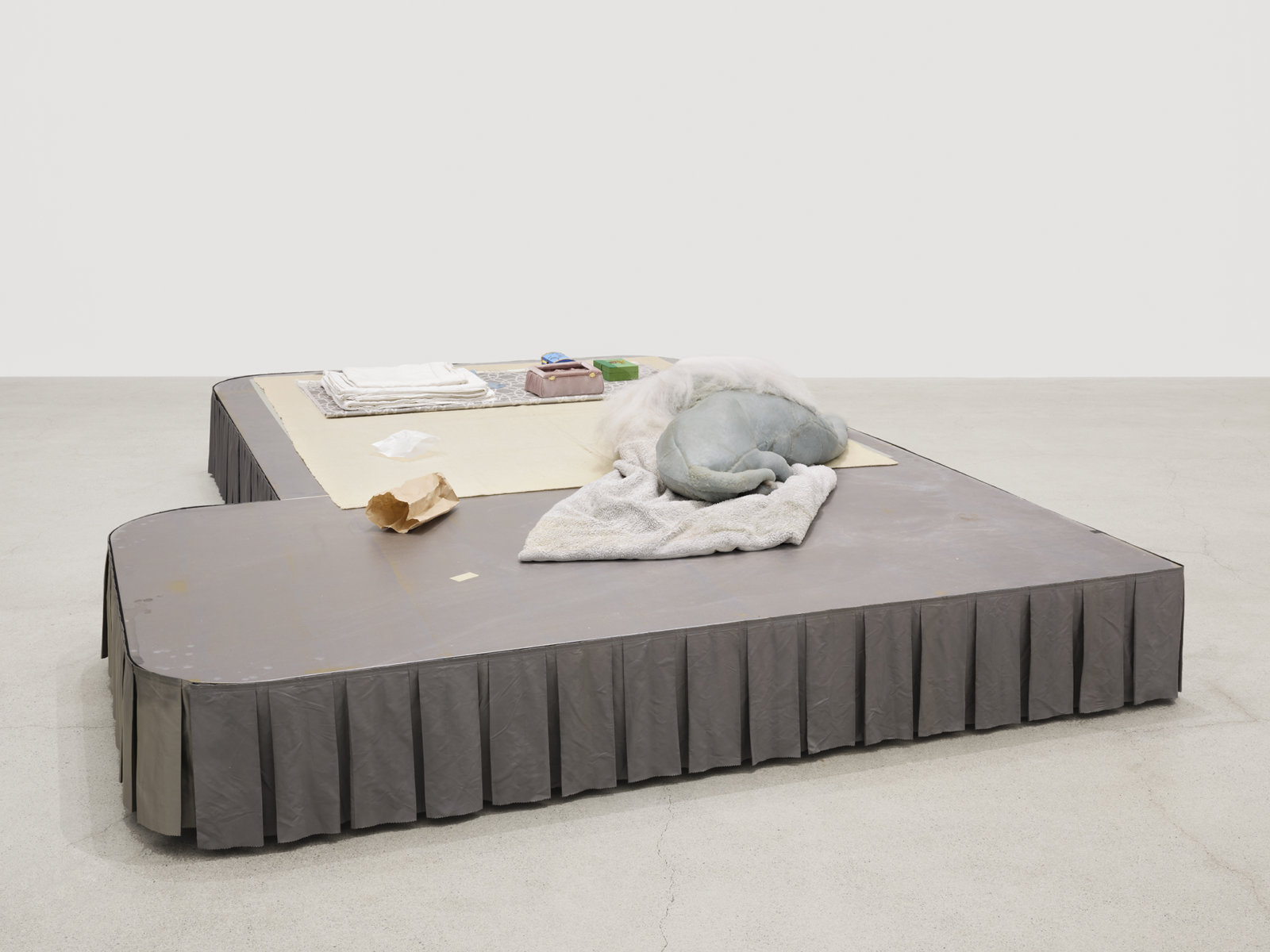 Liz Magor, Coiffed, 2020, painted plywood, fabric skirting, silicone rubber, artificial hair, acrylic throw, woollen blankets, silver fabric, linen, jewellery boxes, costume jewellery, packaging materials, 27 x 132 x 96 in. (69 x 335 x 244 cm) by Liz Magor