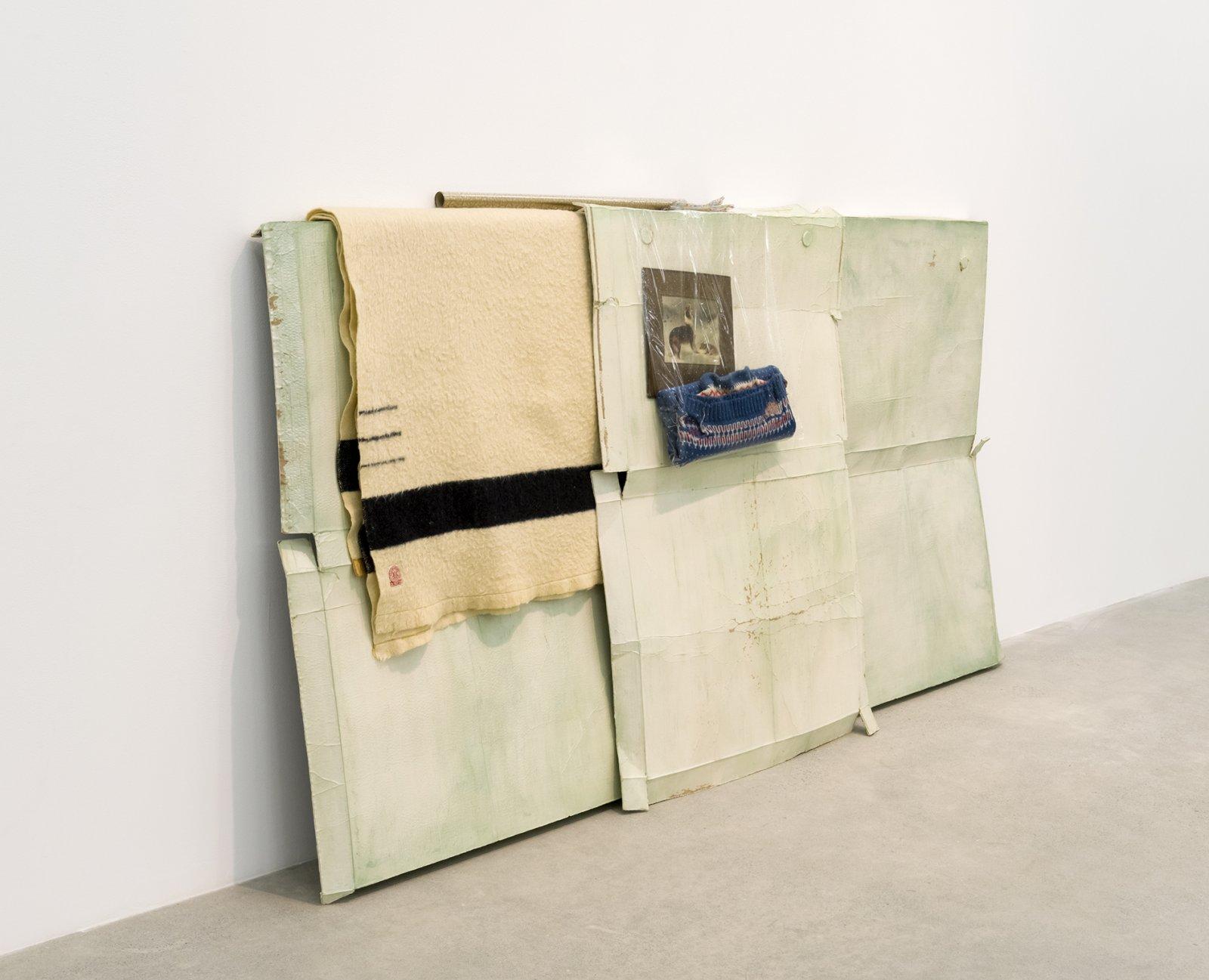 Liz Magor, Good Shepherd, 2016, polymerized gypsum, wool, plastic bags, plastic sheet, cardboard, 53 x 103 x 12 in. (133 x 262 x 31 cm) by Liz Magor