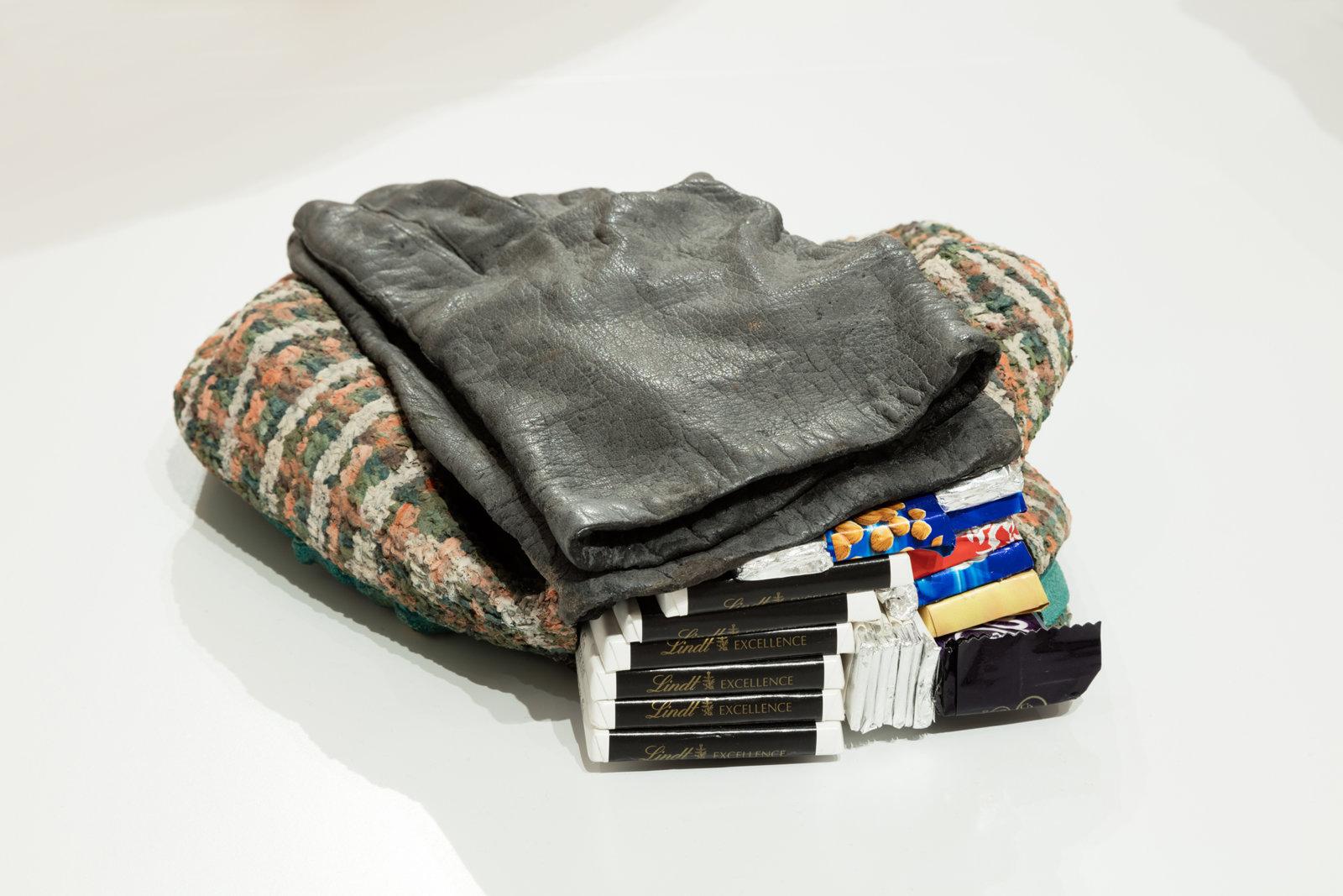Liz Magor, Hat and Gloves, 2007, polymerized gypsum, chocolate bars, 4 x 8 x 10 in. (9 x 21 x 25 cm). Installation view, Habitude, Musée d'art contemporain de Montréal, 2016 by Liz Magor