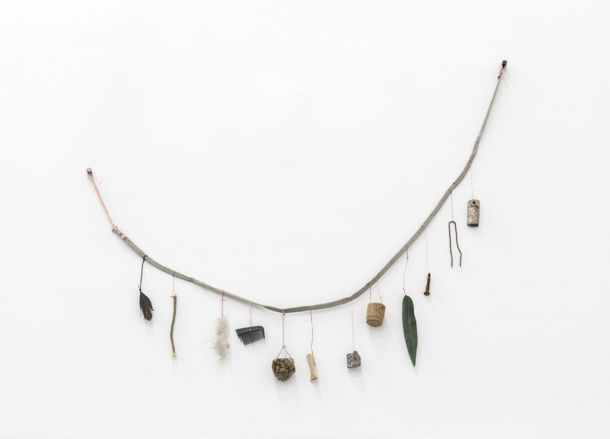 Gareth Moore, Reminder (Vancouver), 2013, shoelace, string, copper wire, wood, metal, artificial leaf, cork, stone, bone, burl, comb, cloth, rope, feather, 19 x 22 x 1 in. (47 x 56 x 2 cm) by