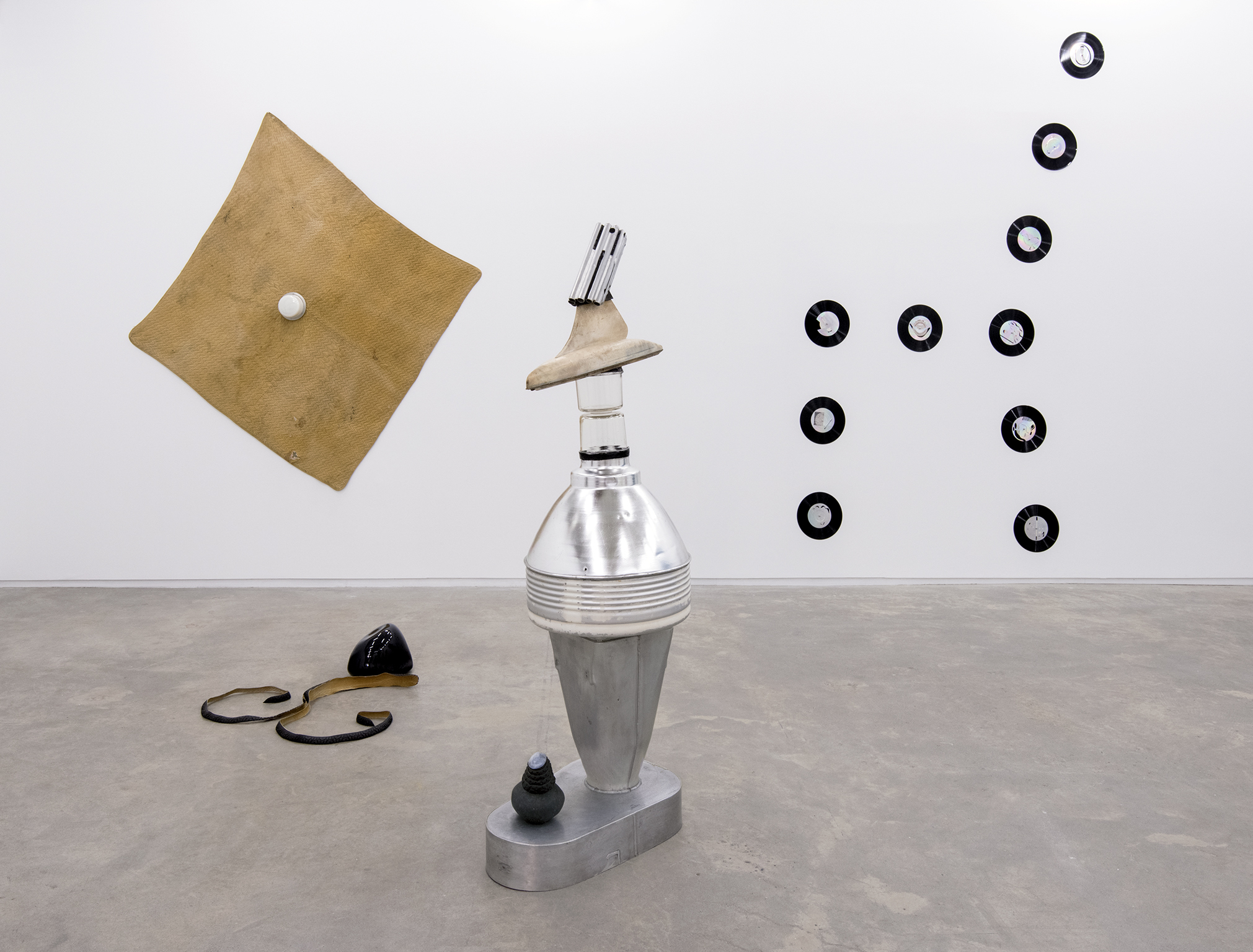 Jerry Pethick, Kolossus of Kindergarden, 1987–1989, spectra-foil on records, aluminium, blown glass, wood, rock, tires, cargo blanket, dimensions variable by