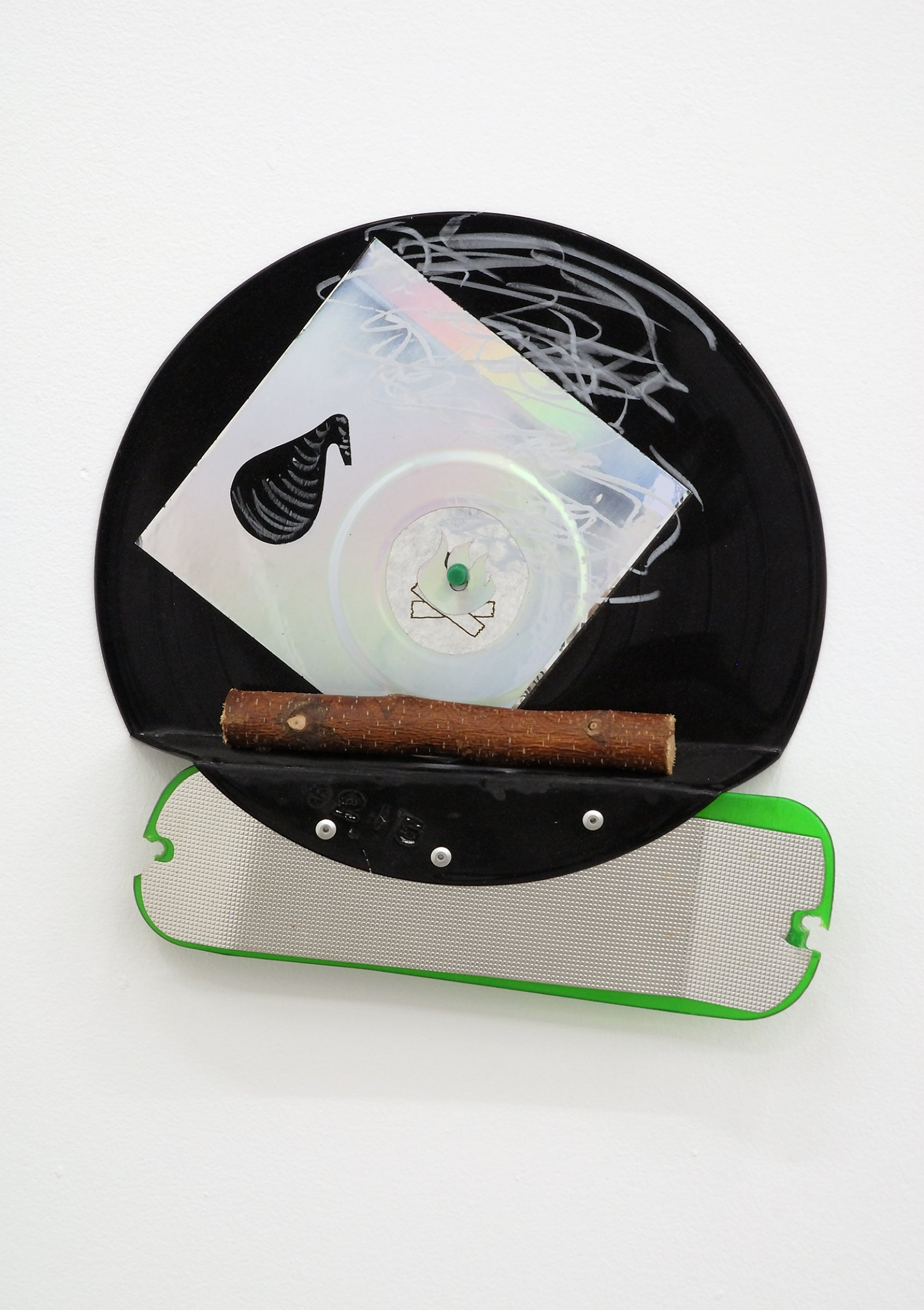 Jerry Pethick, Black Retort Travelogue, 1991/1992, Phonograph record, crayon, spectrafoil, plastic fishing lure, piece of wooden branch, metal screws, 12 x 13 x 2 in. (30 x 32 x 5 cm)   by Jerry Pethick