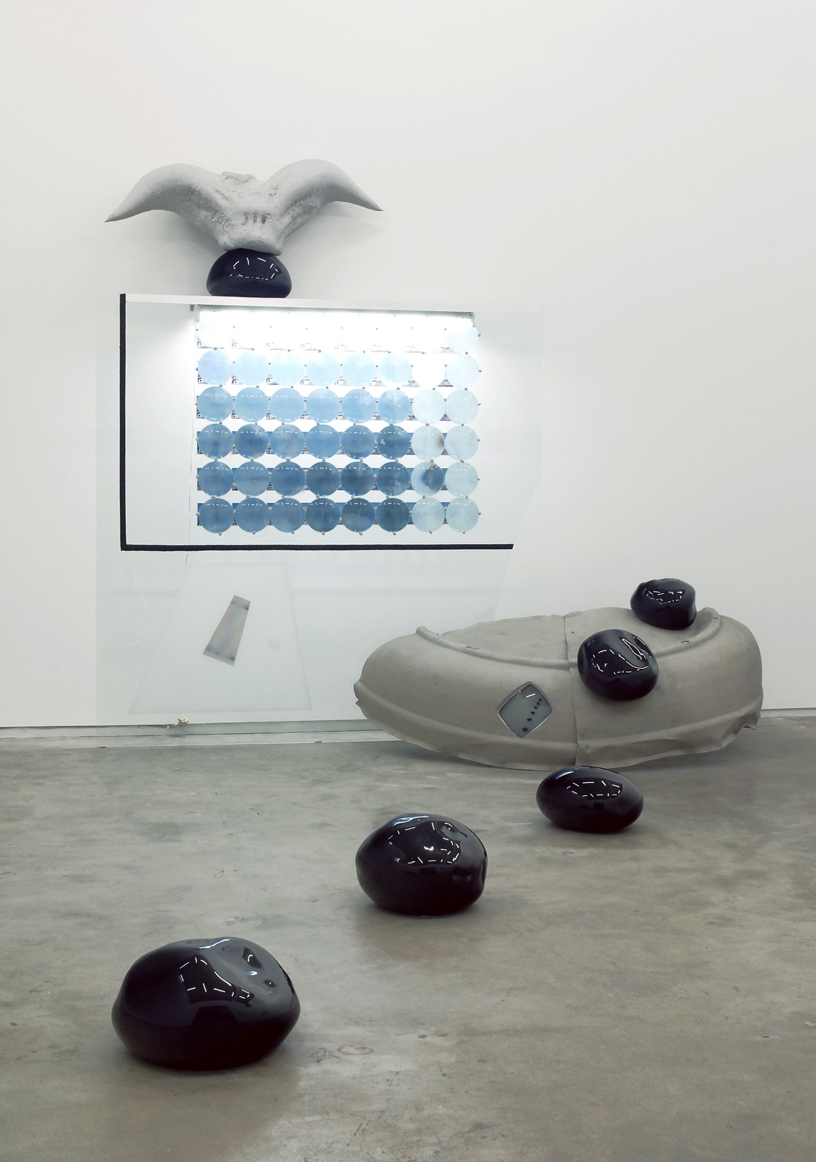 Jerry Pethick, Roof to Heaven Too, 1986–1988, blown glass, glass, rubber tire, TV tube, stones, aluminum, spectrafoil, 48 instamatic prints, 48 blue fresnel lenses, styrofoam, silicone, fluorescent light fixture, 169 x 111 x 75 in. (429 x 282 x 191 cm) by Jerry Pethick