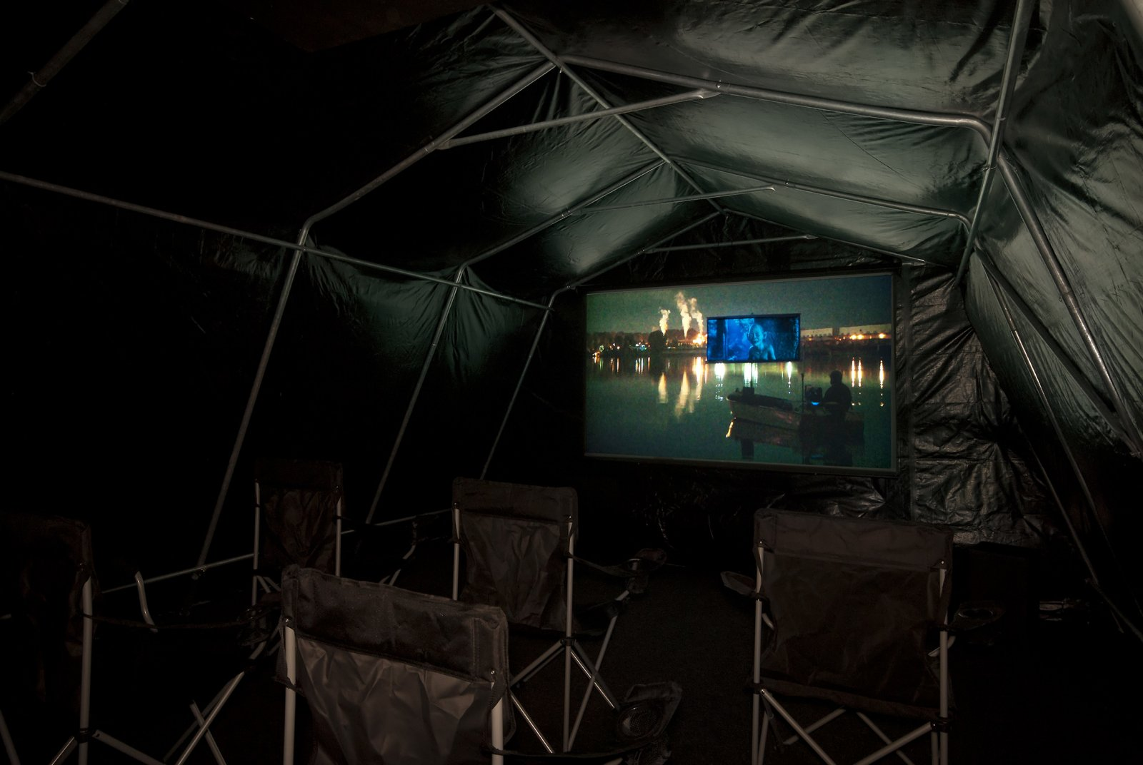 Kevin Schmidt, Autonomous Projection Room #1, 2010, tarp, portable garage frame, carpet, roxul, projector, home stereo system, screen, batteries, inverter, camping chairs, 181 x 60 x 105 in. (460 x 152 x 267 cm) by Kevin Schmidt