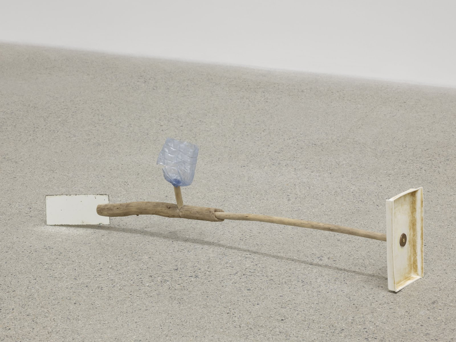 Ashes Withyman, Under a mouldy sky (spent tire, slab of stone, torn barbed wire fence), 2019, branches, margarine container base, penny, portion of water bottle, mirror, 7 x 26 x 4 in. (18 x 66 x 10 cm) by Ashes Withyman